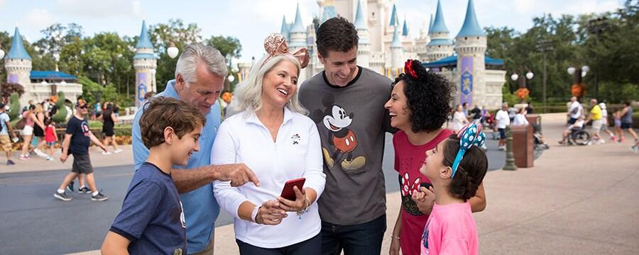 Uma família alegre consultando o telefone celular em frente ao Cinderella Castle