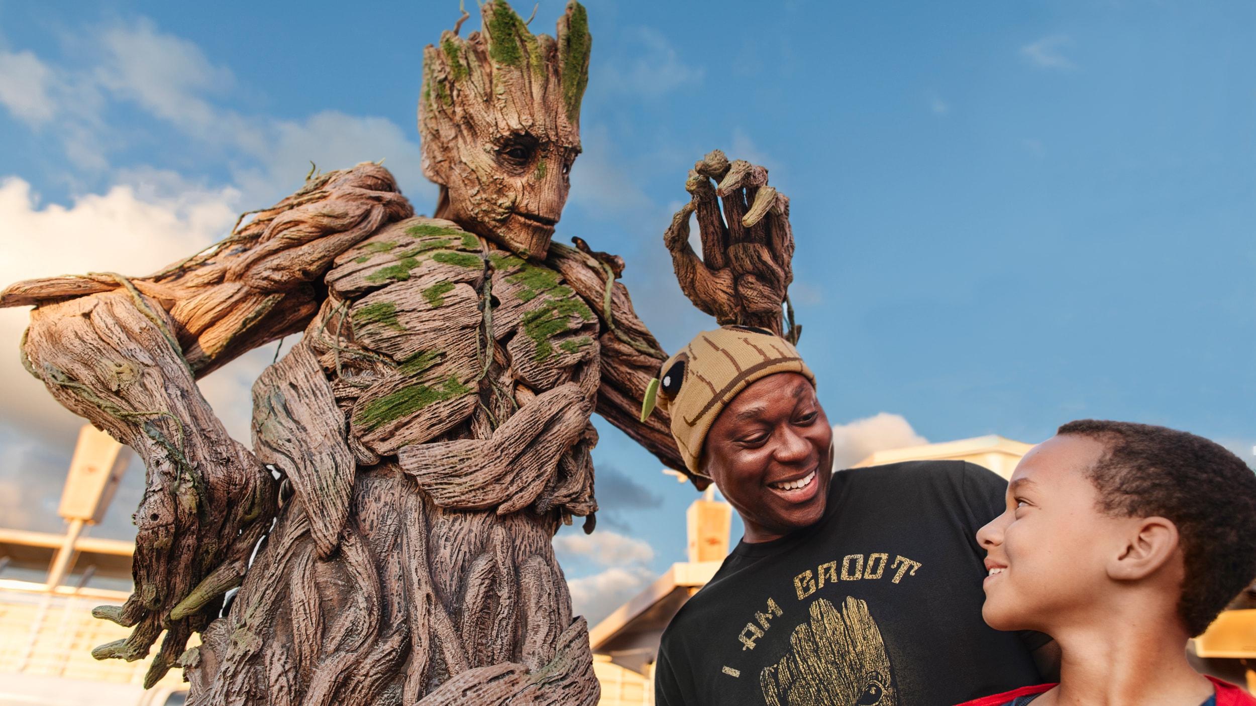 Um homem e um menino estão ao lado do Groot