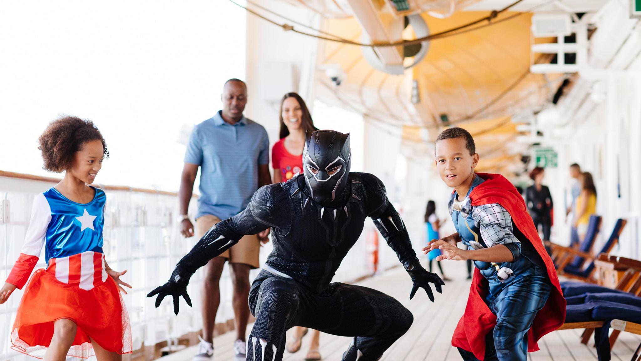 Pantera Negra se agacha, pronto para a ação, enquanto 2 crianças imitam sua pose em um Cruzeiro Disney