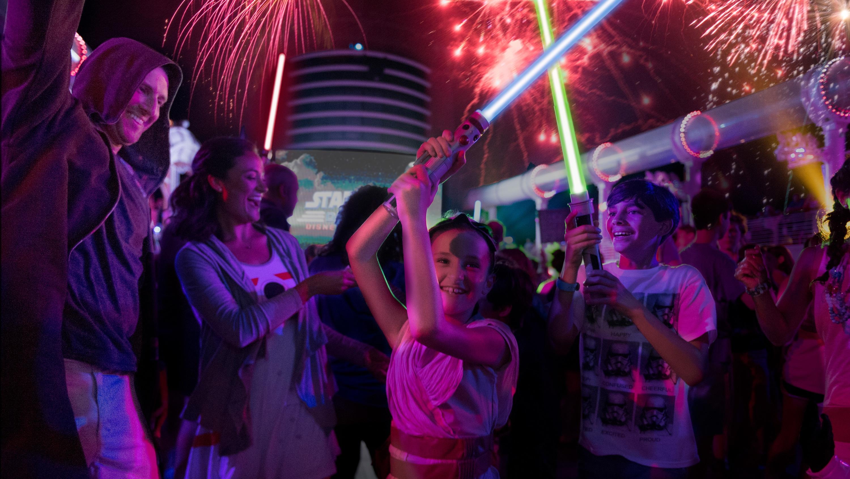 Família brinca com sabres de luz em um Cruzeiro Disney, enquanto fogos de artifício estouram ao fundo
