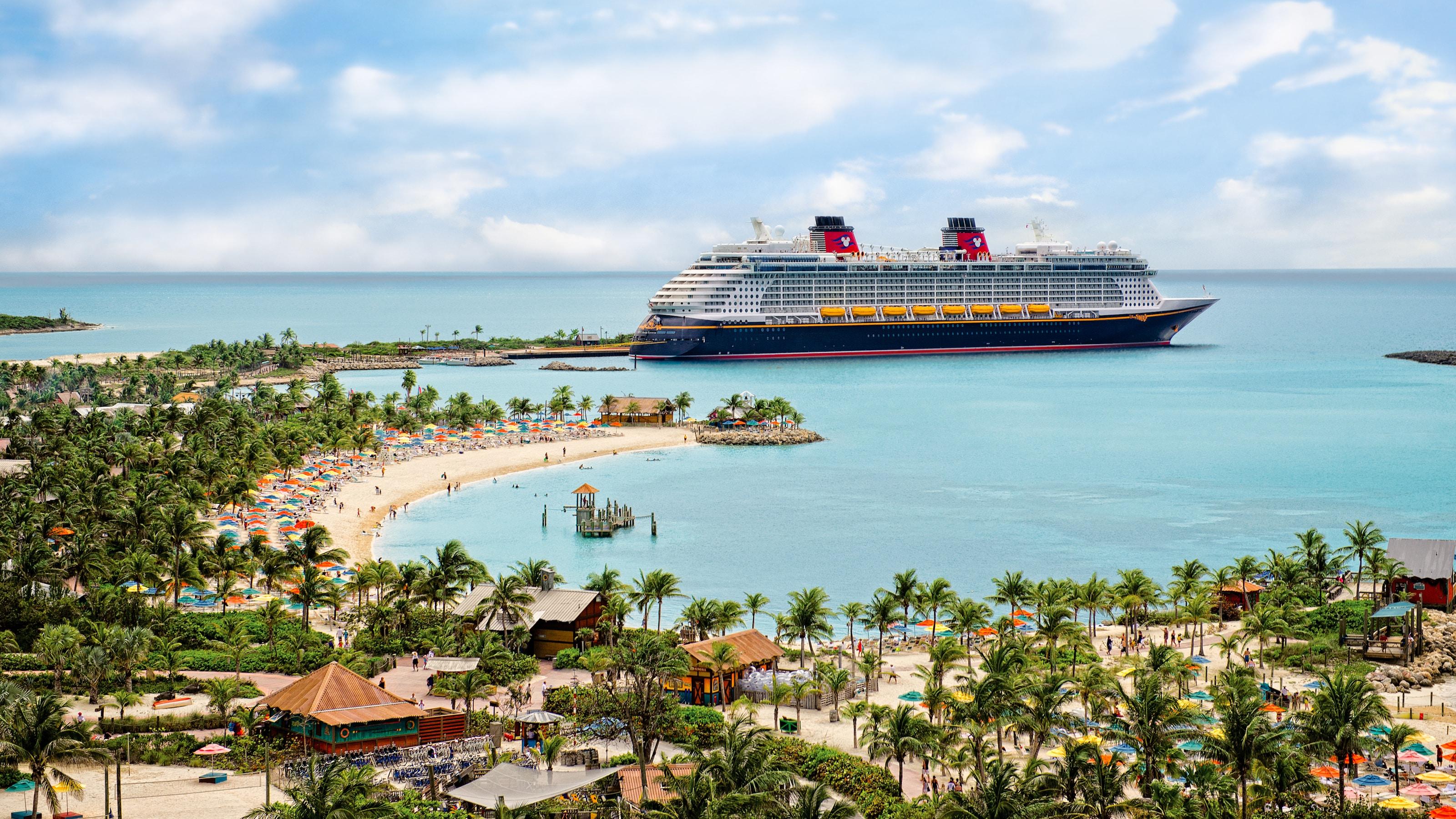 Um navio da Disney Cruise Line ancorado perto de uma praia onde há guarda-sóis, pessoas e palmeiras