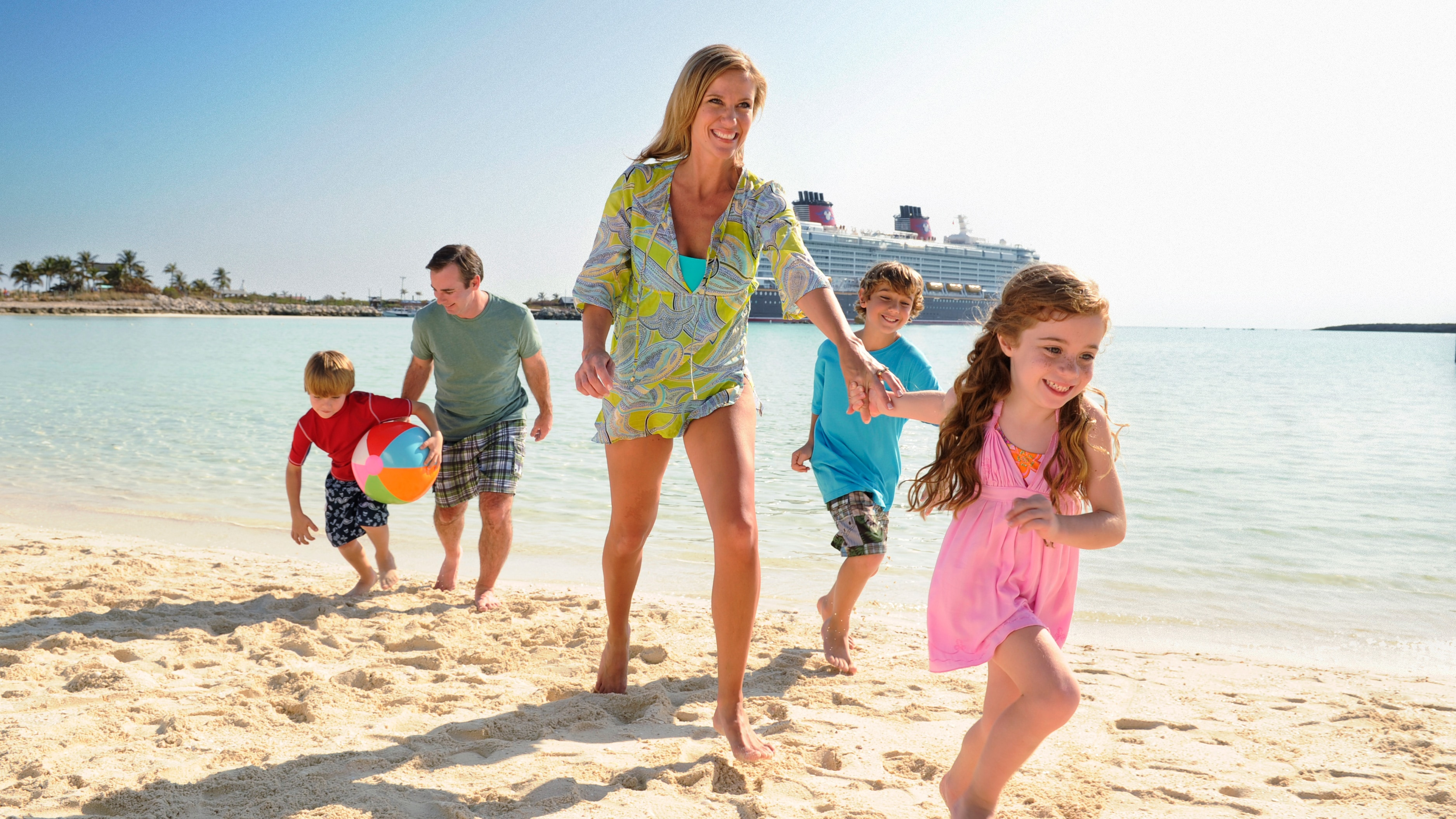 Uma família de 5 pessoas passeia em uma praia com um navio da Disney Cruise Line atracado ao fundo