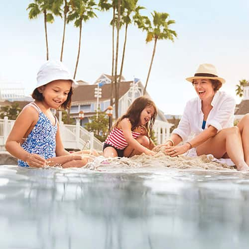 A mother and her 2 daughters build a sand castle at Disney's Beach Club Resort