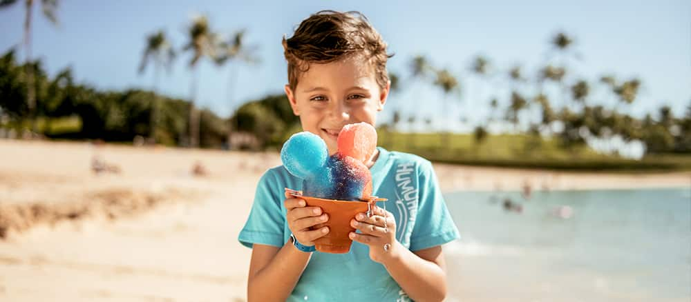 A boy stands on a tropical beach near the ocean and holds a bucket containing a Mickey Mouse balloon