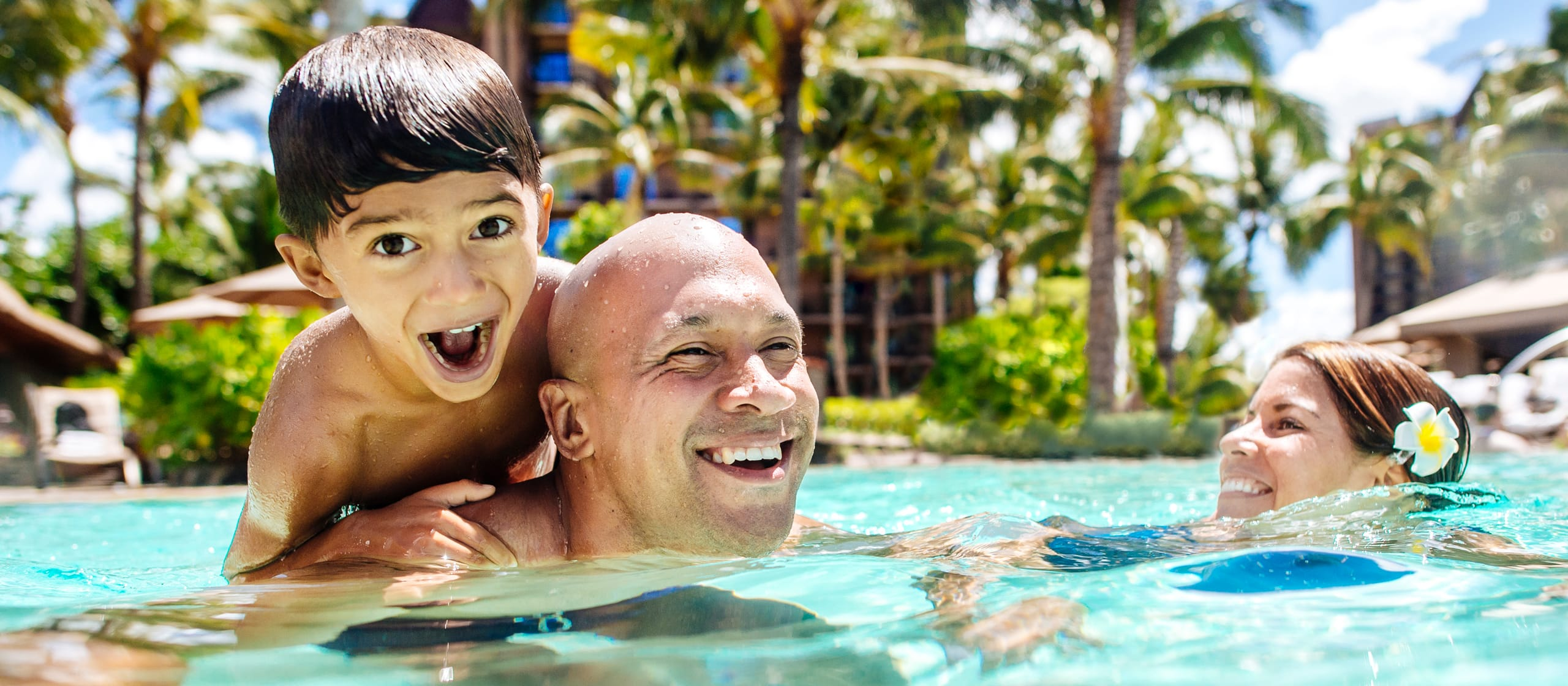 In sparkling blue water, a mother and father, his young son perched on his back, smile as they enjoy swimming together