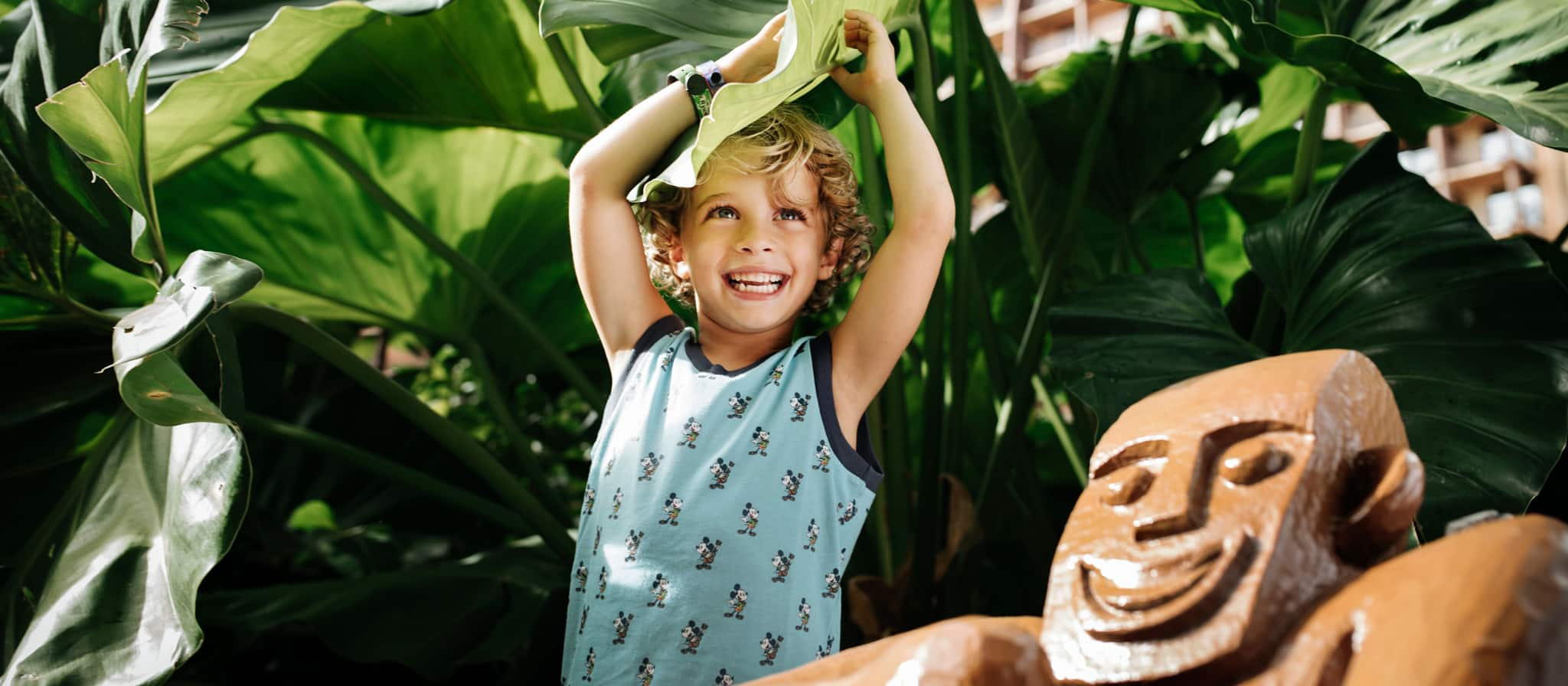 A smiling toddler, standing next to a menehune statue, pulls a large taro leaf on top of her head