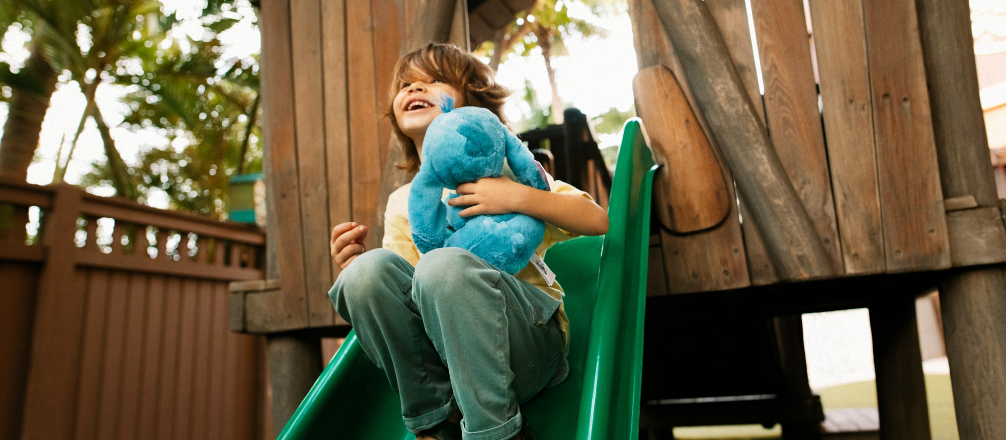 A young boy goes down a slide holding a Stitch plush
