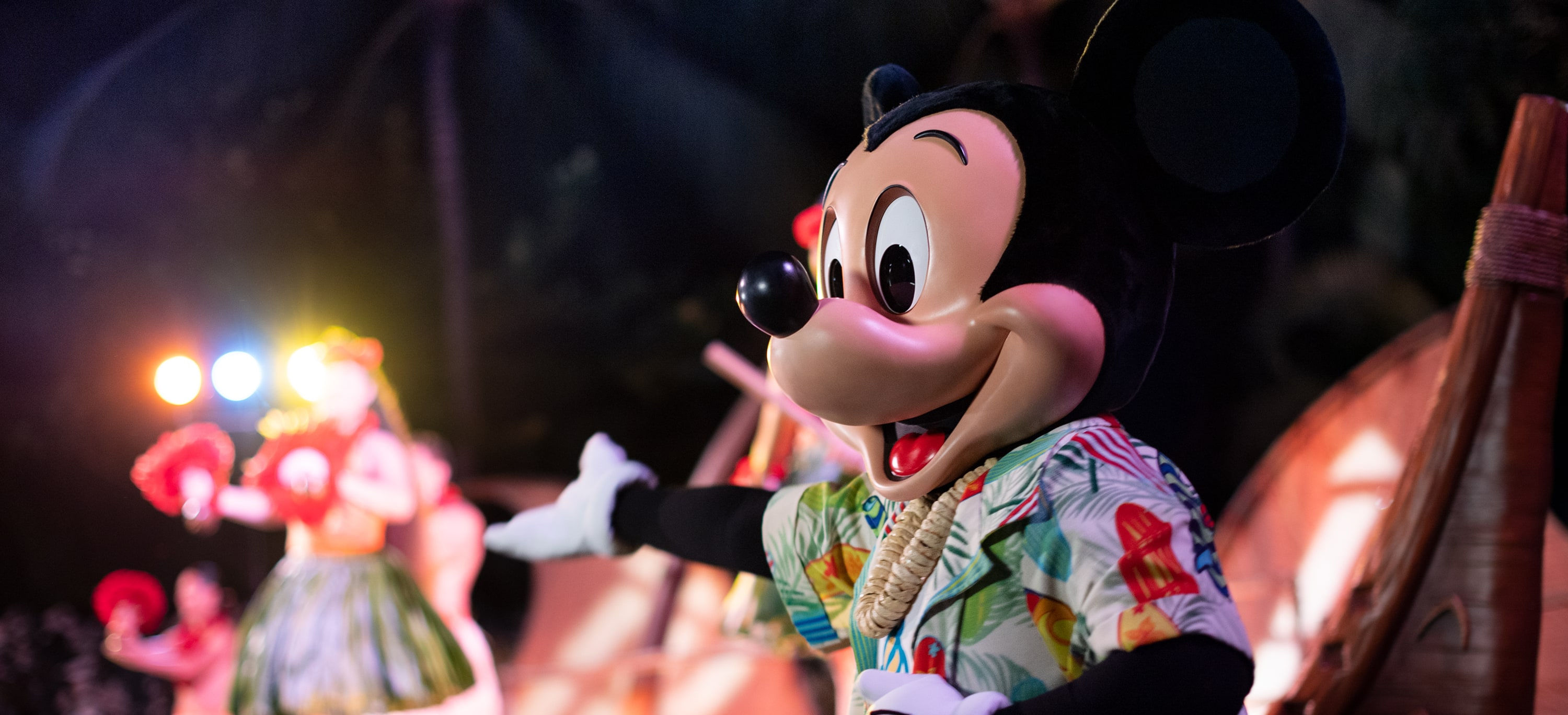Mickey Mouse, wearing a Hawaiian shirt and a shell lei, joins performers on stage at night