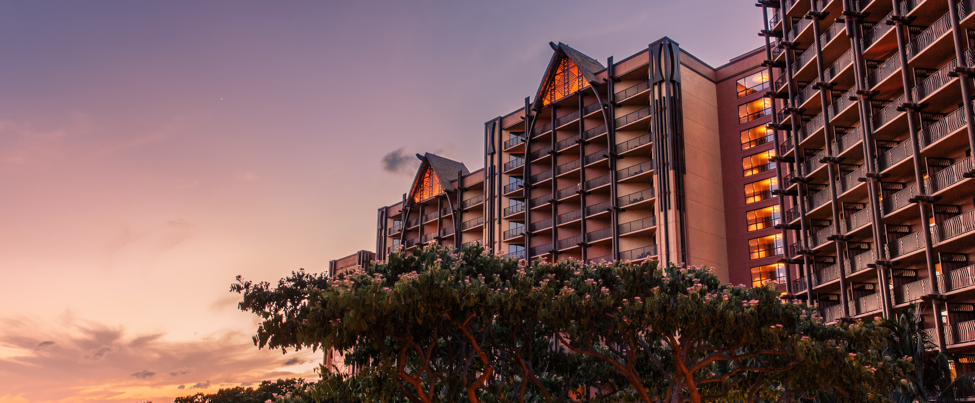 The towers of Aulani Resort & Spa as seen at twilight with a flowering tree in the foreground