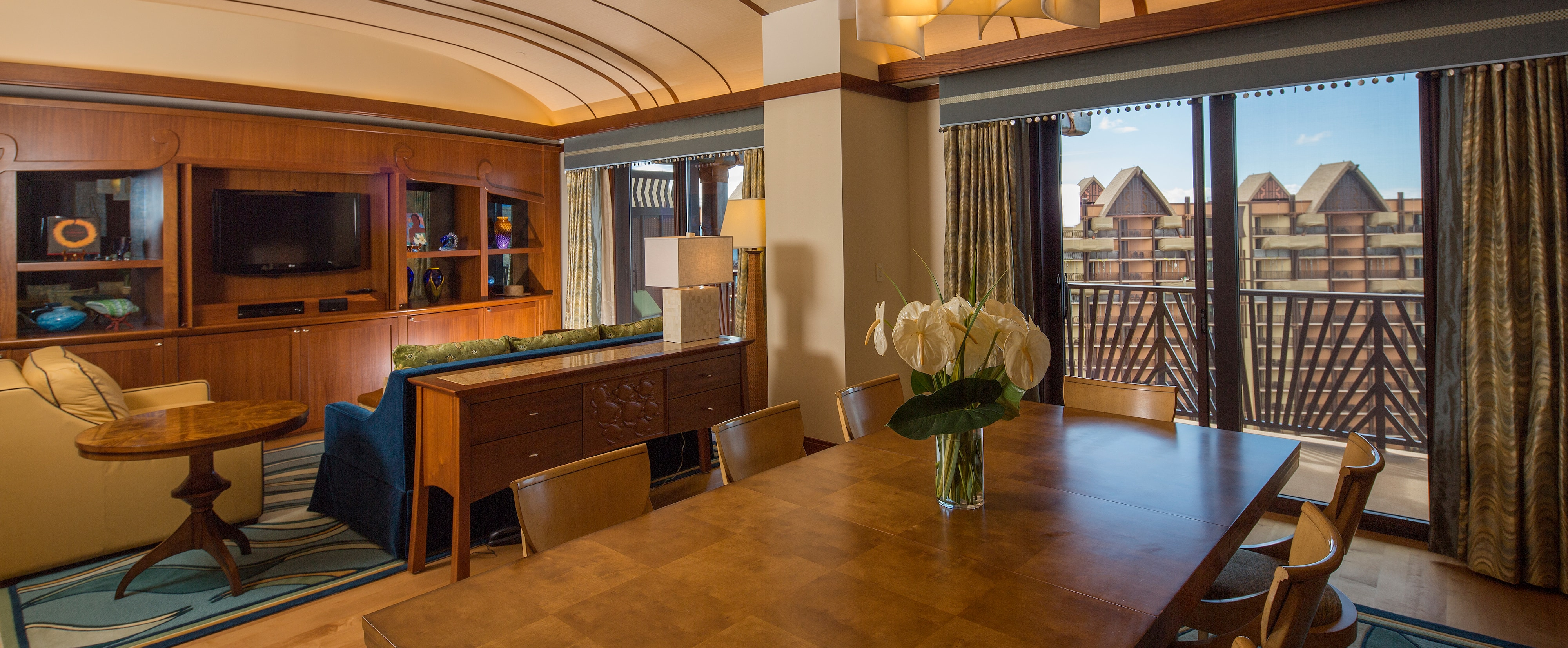 The living area, dining area and balcony of the Deluxe 1-Bedroom Suite