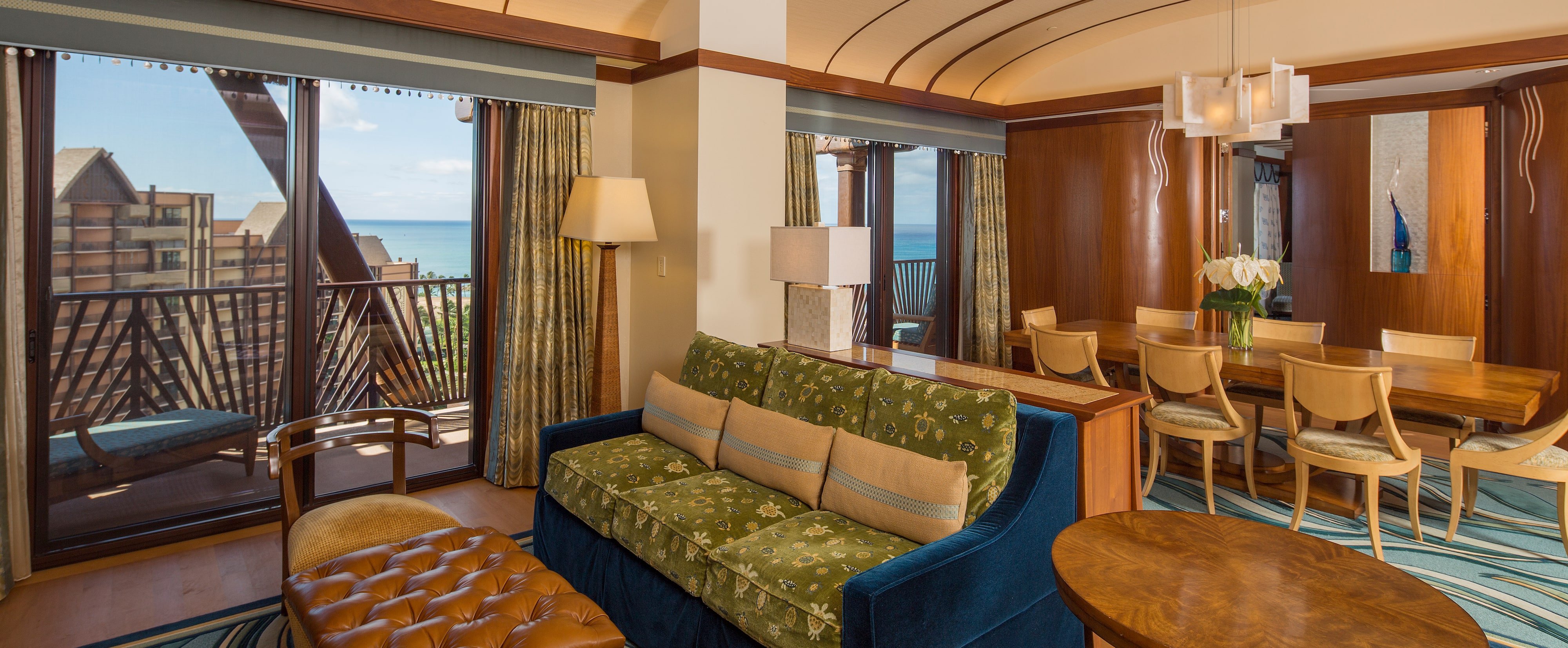 The living area, dining area and entertainment center of the Deluxe 1-Bedroom suite