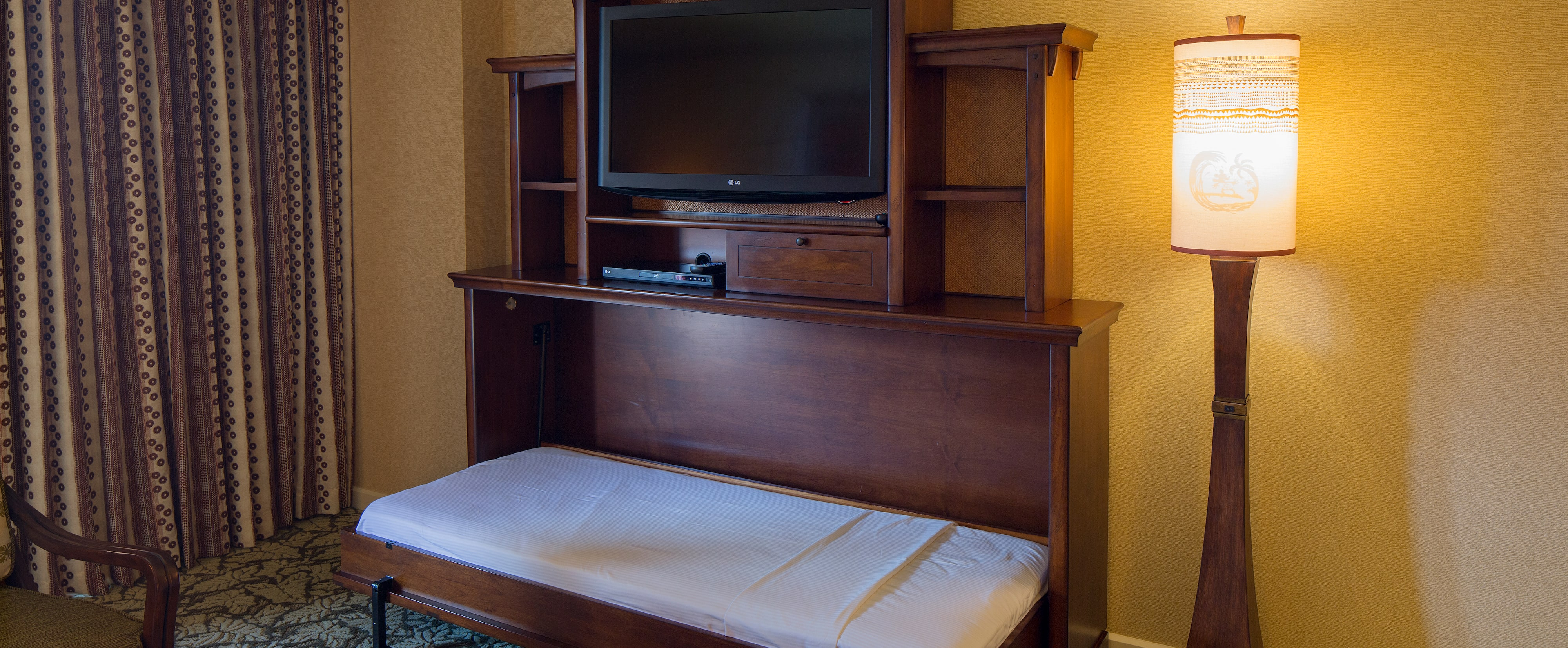A pull-down bunk in the entertainment center of the 1-Bedroom Suite