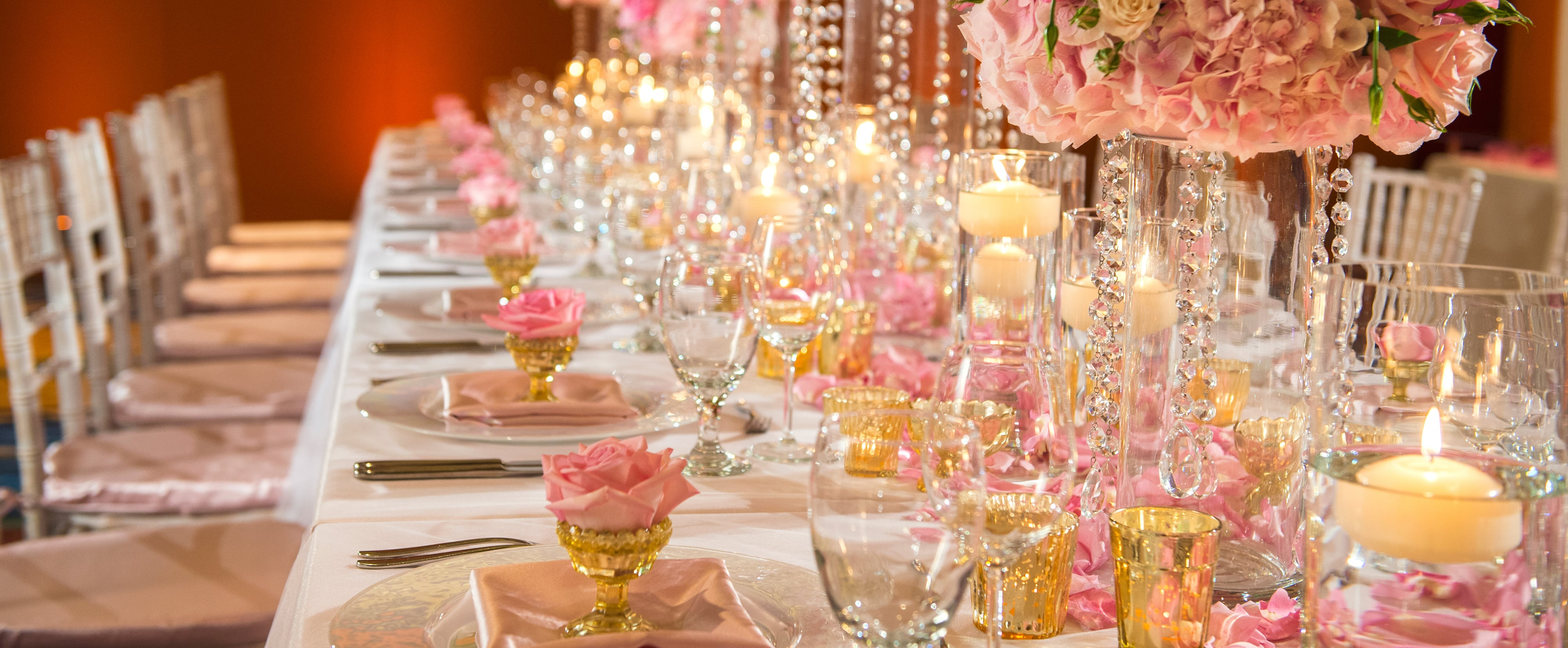 A dinner table in Ka'ala Ballroom decorated with pink roses and pearls