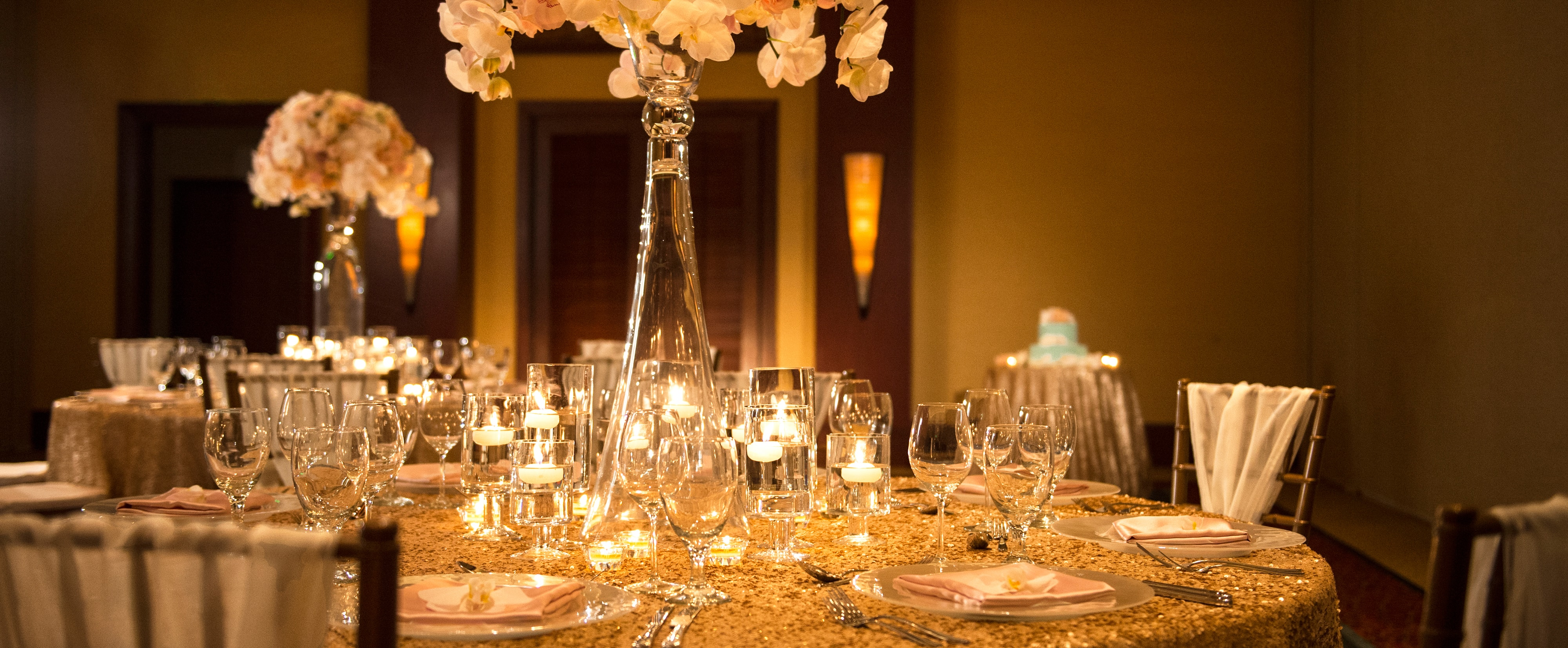 A dinner table in Kaiona Ballroom decorated with flowers and candles