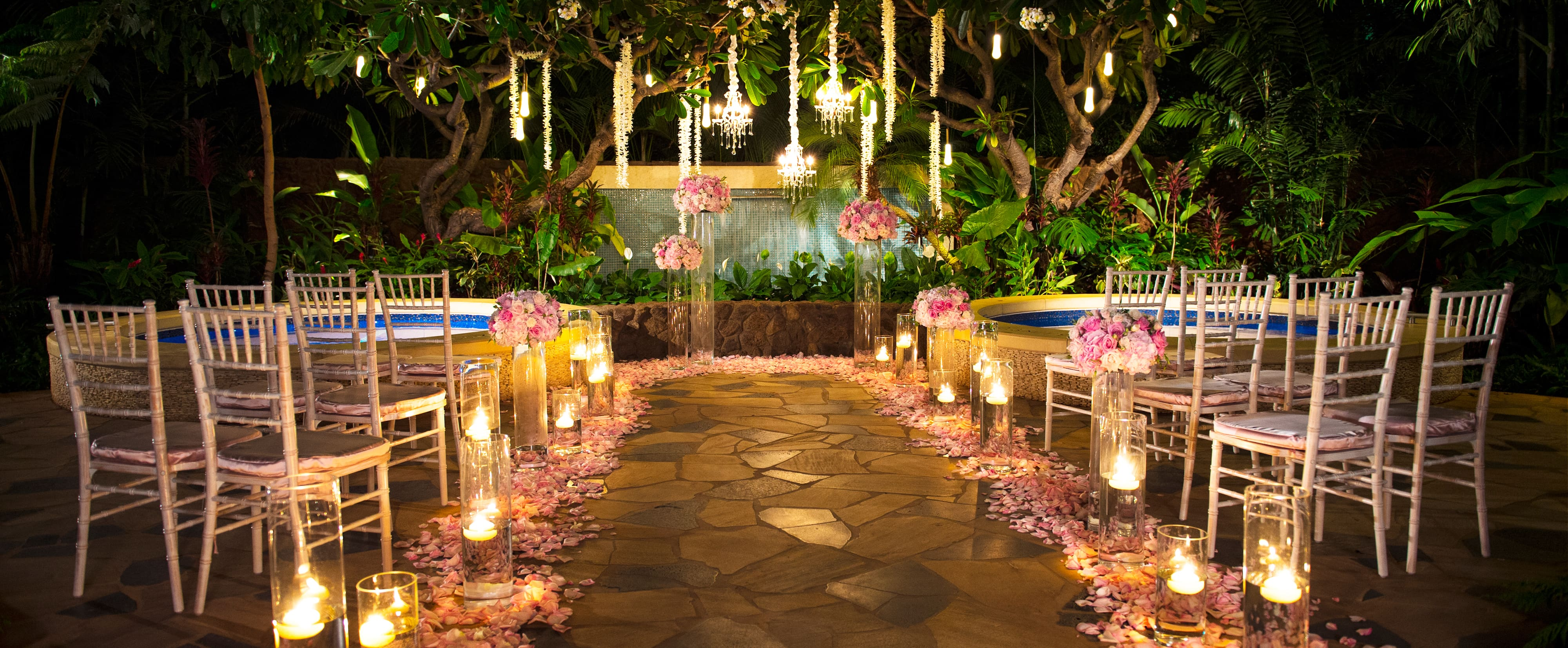 Kula Wai garden set up for a wedding, with flowers, chandeliers and chairs