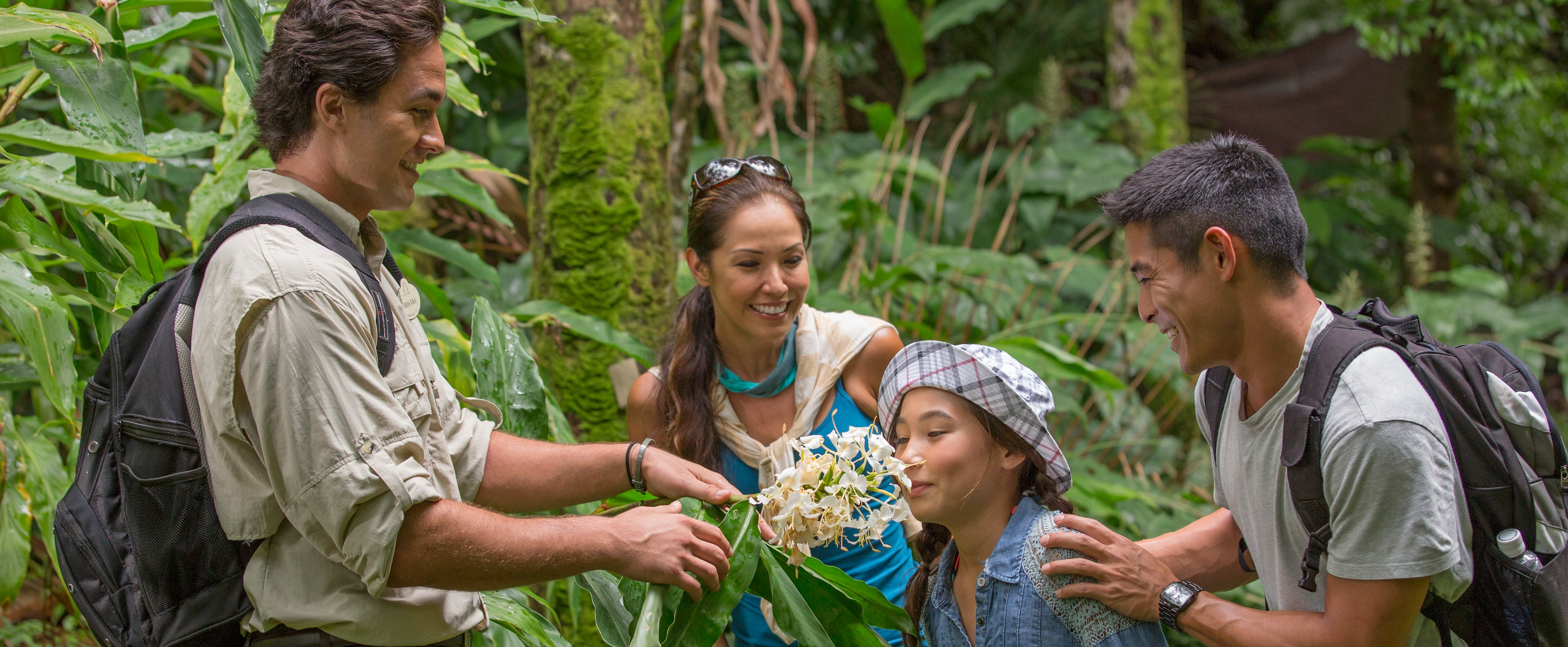 A family learns about flowers on an Oʻahu nature hike