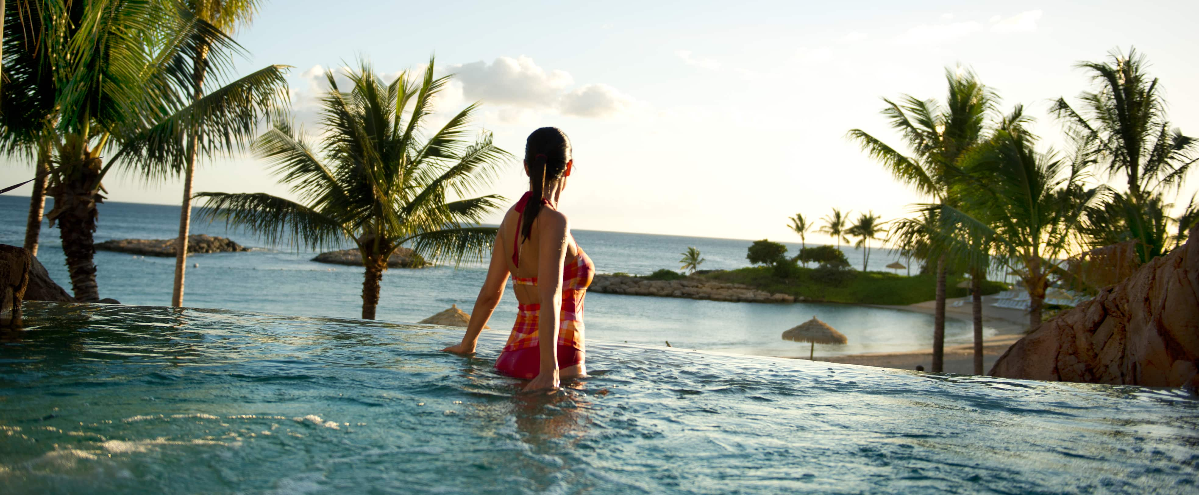 A woman enjoys ocean views from the whirlpool spa at Aulani