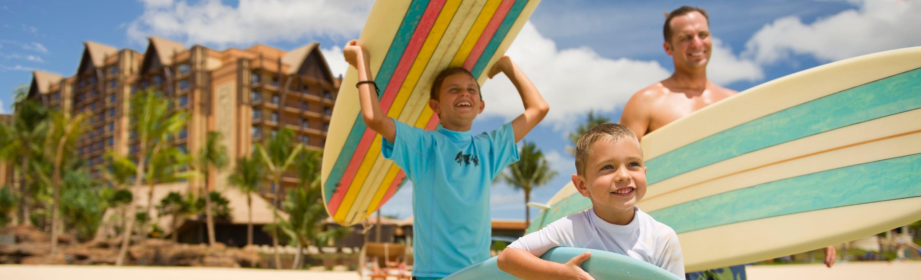サーフボードを持って海の方へ歩く父親と 2 人の息子