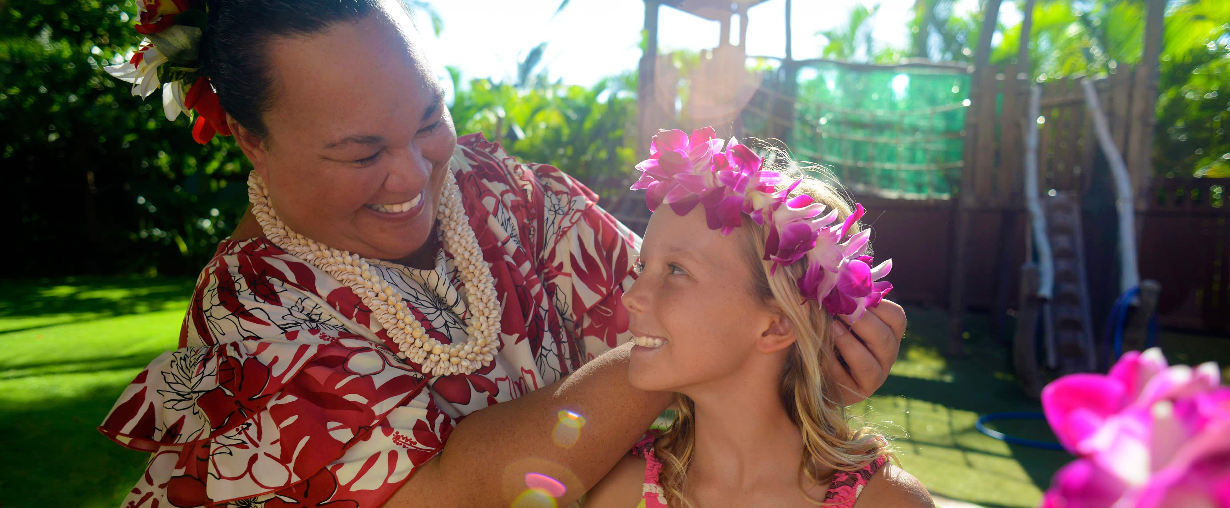 Auntys beach house kids club aulani hawaii resort spa a smiling woman in hawaiian garb puts a fuchsia orchid wreath on a young girls head izmirmasajfo