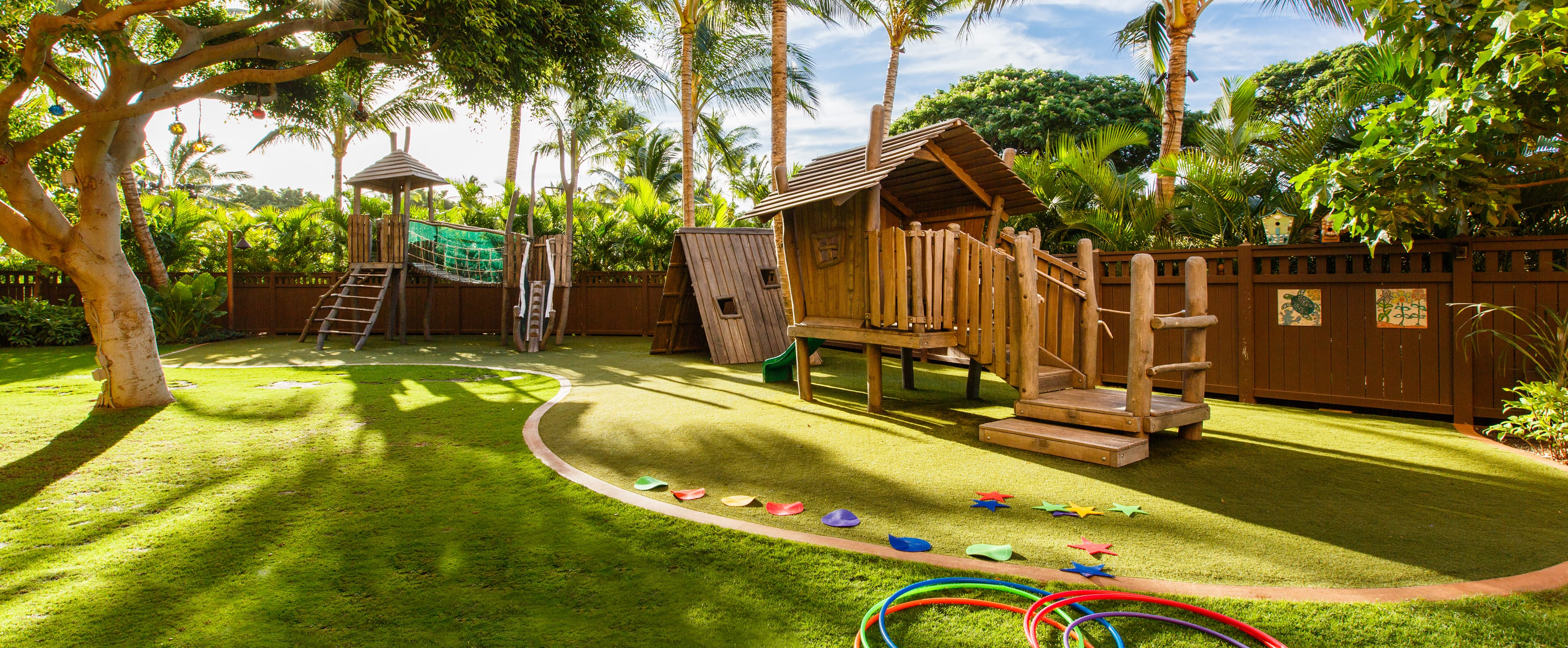 A grassy playground area with 2 wooden climbing structures, a playhouse and hula hoops on the lawn