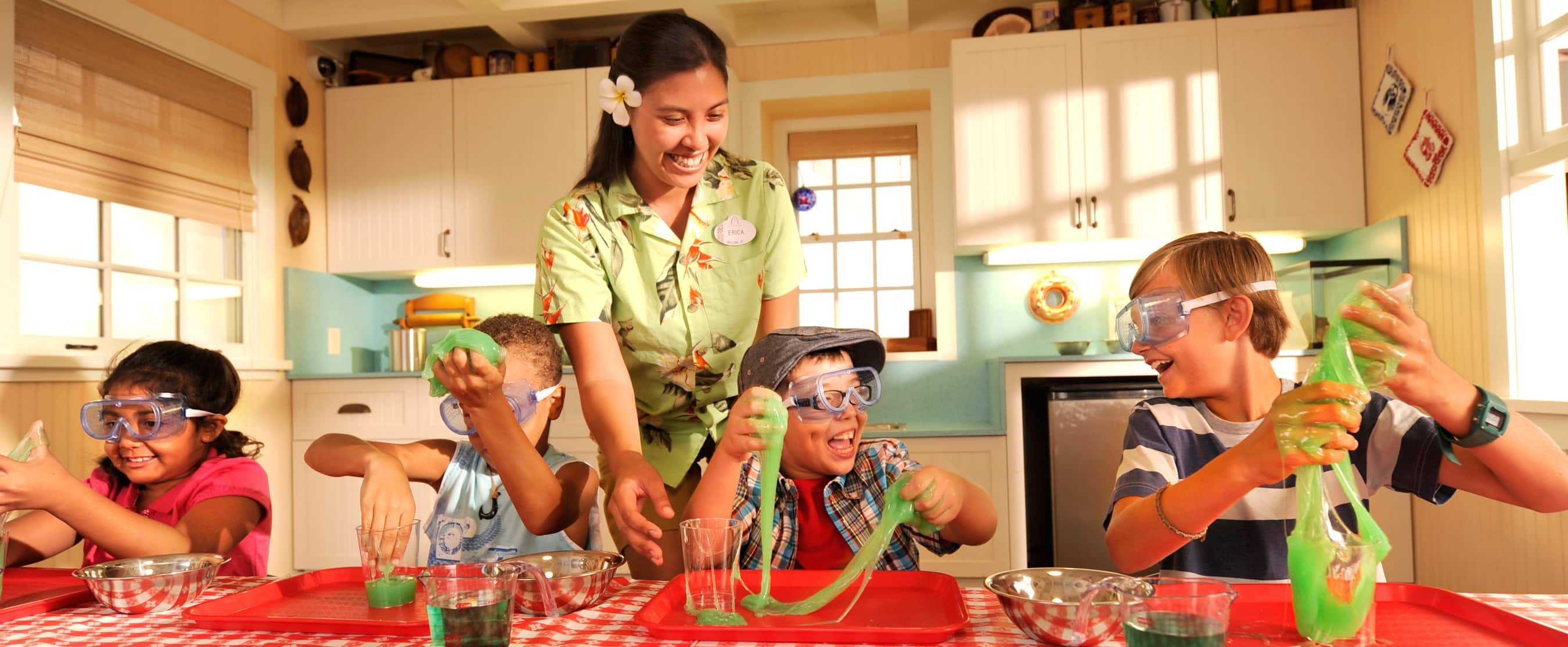 A Cast Member supervises 4 children wearing goggles and playing with green slimeA Cast Member supervises 4 children wearing goggles and playing with green slime