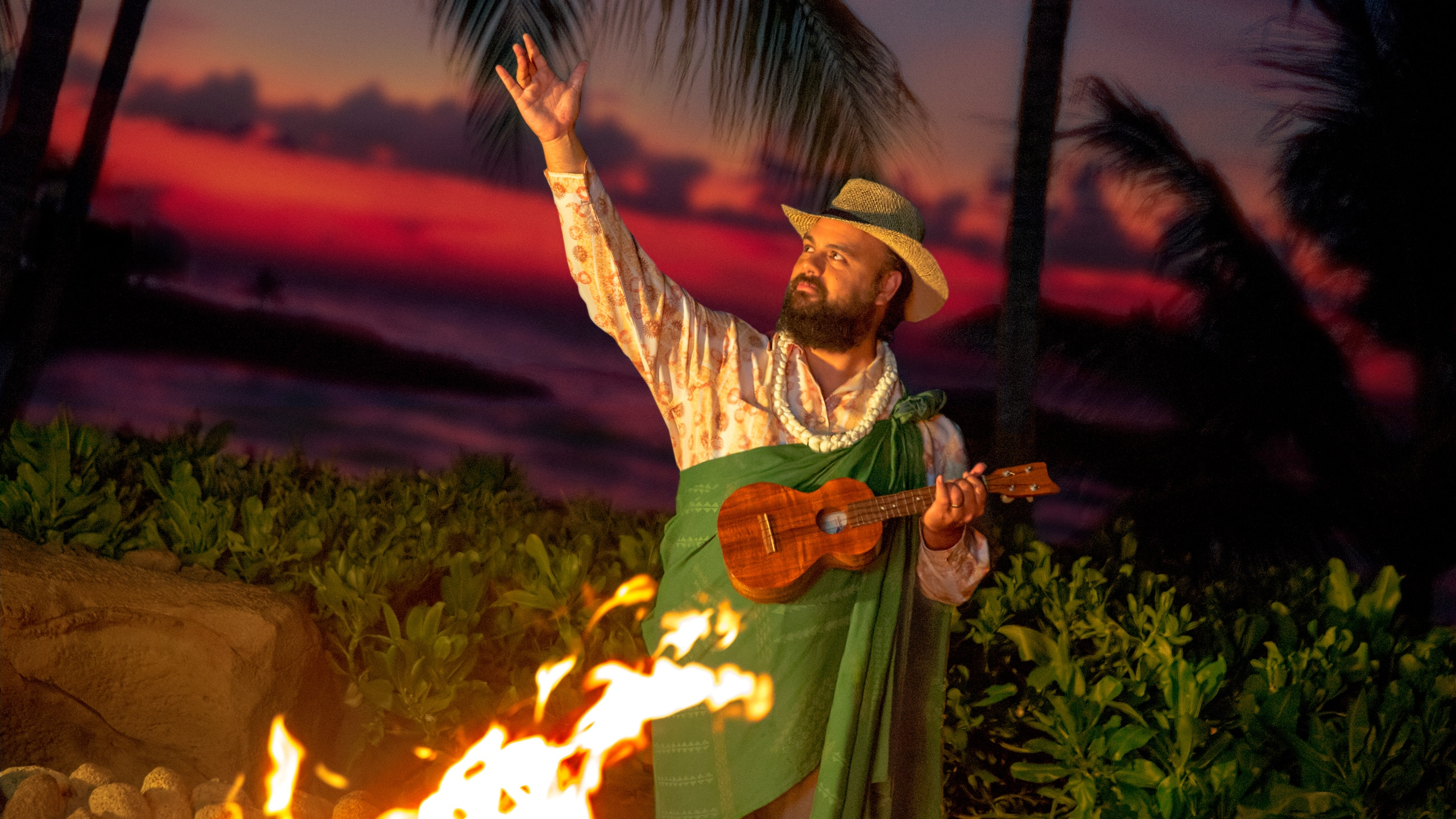 Uncle stands beside the fire pit holding a ukulele and gesturing to the night sky