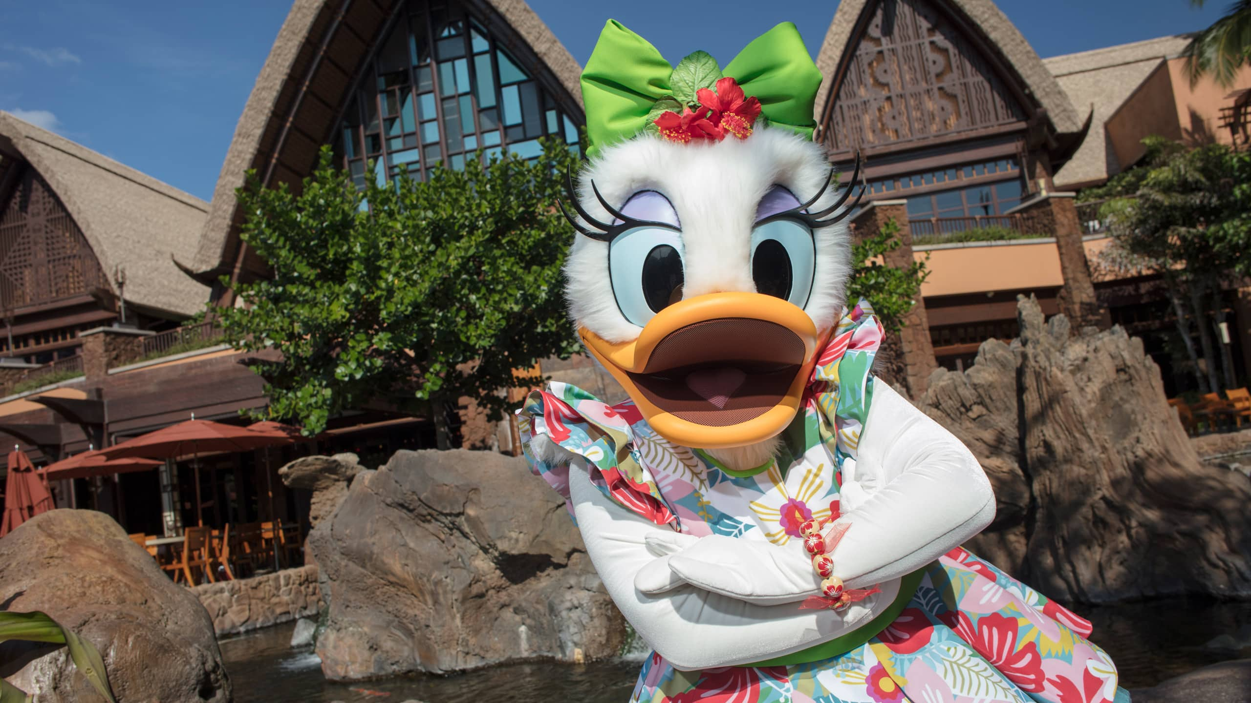 Daisy Duck poses with her arms crossed and wearing a Hawaiian print dress and a bow on her head, in front of the main entrance to Aulani Resort