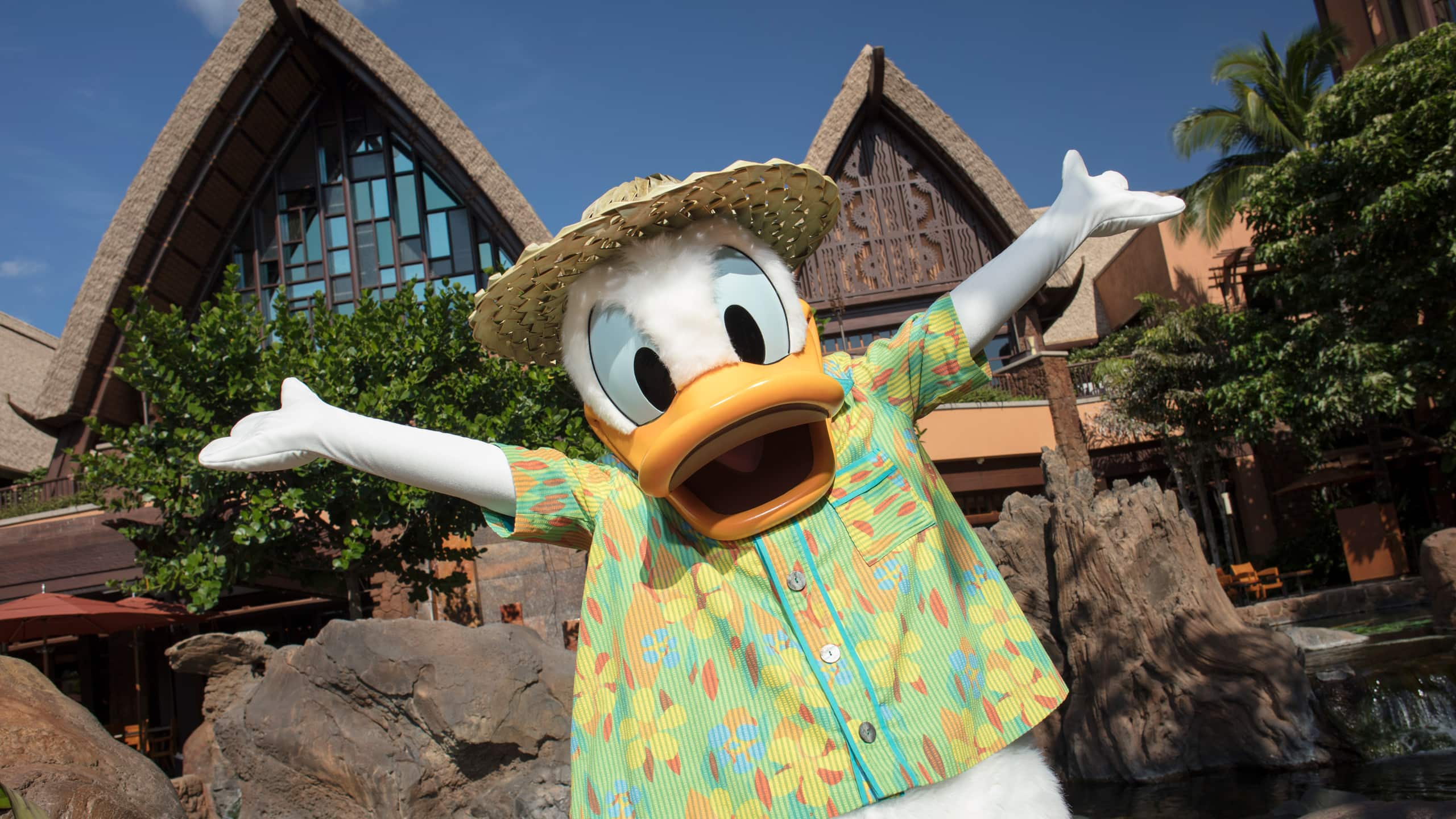 Donald Duck, in a Hawaiian outfit with arms outstretched, in front of the main entrance to Aulani Resort