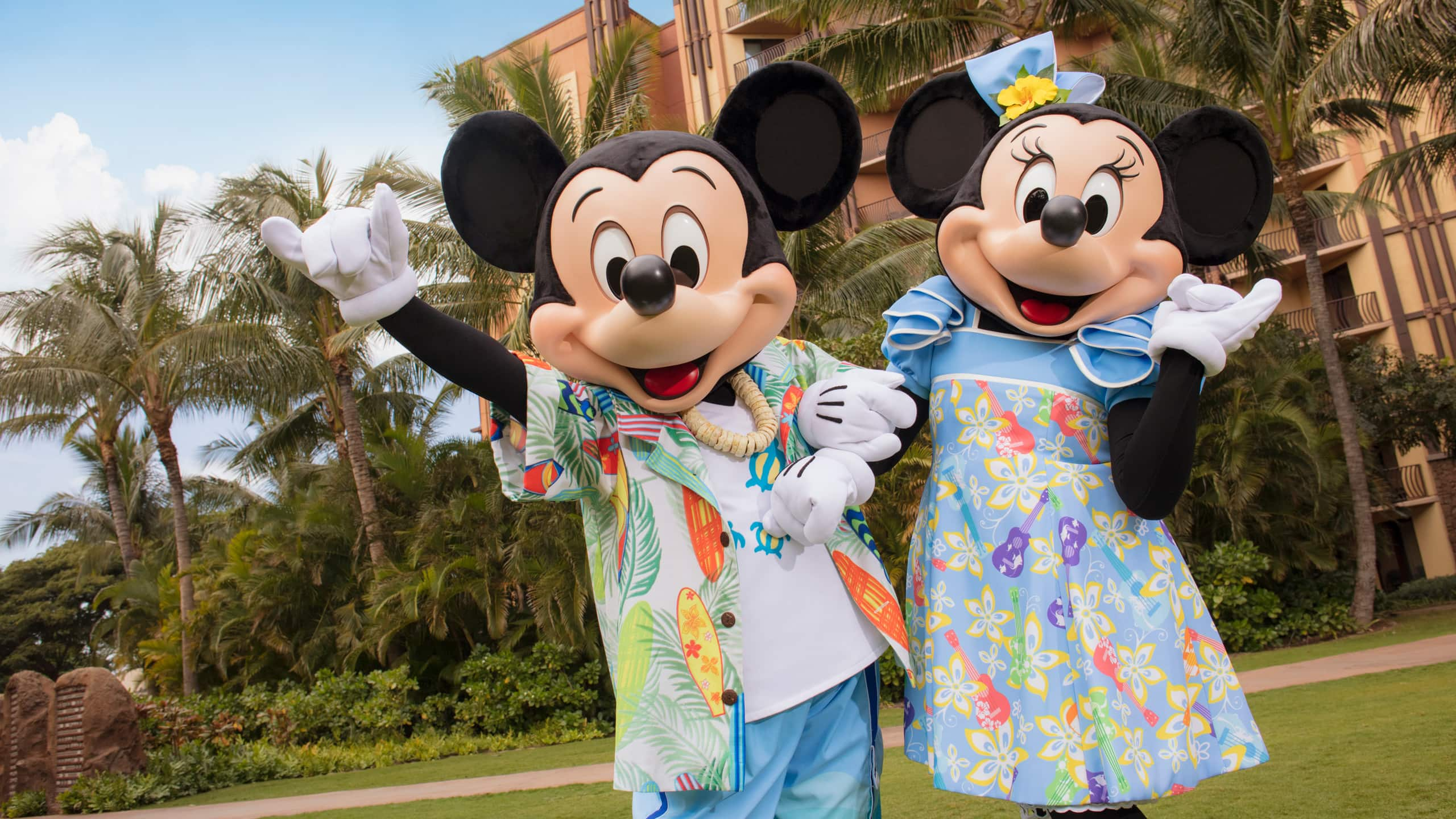 Mickey Mouse and Minnie Mouse, dressed in Hawaiian-style outfits, stand in front of a wing of Aulani Resort