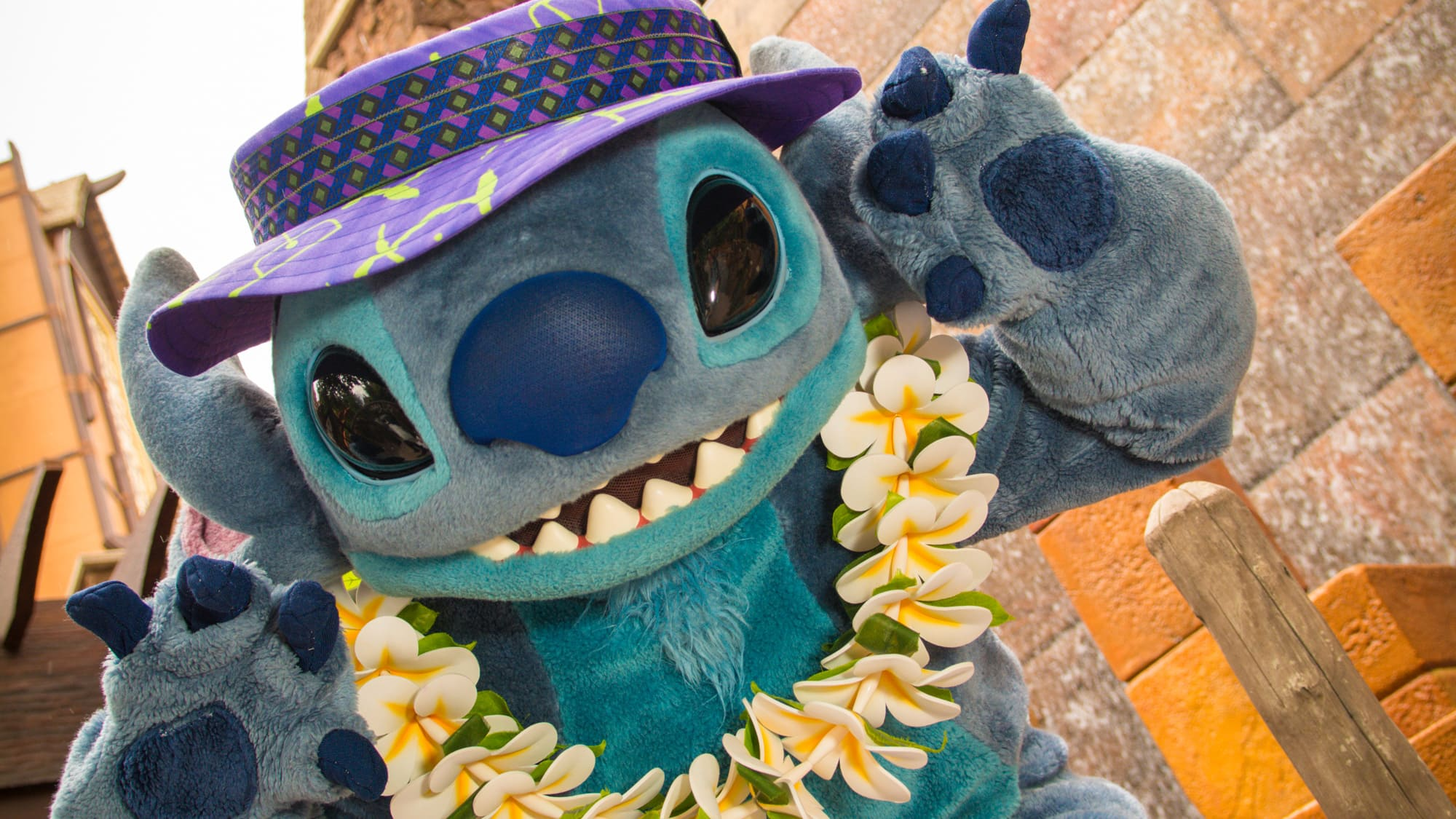 Stitch wears a lei and poses in front of Aulani Resort