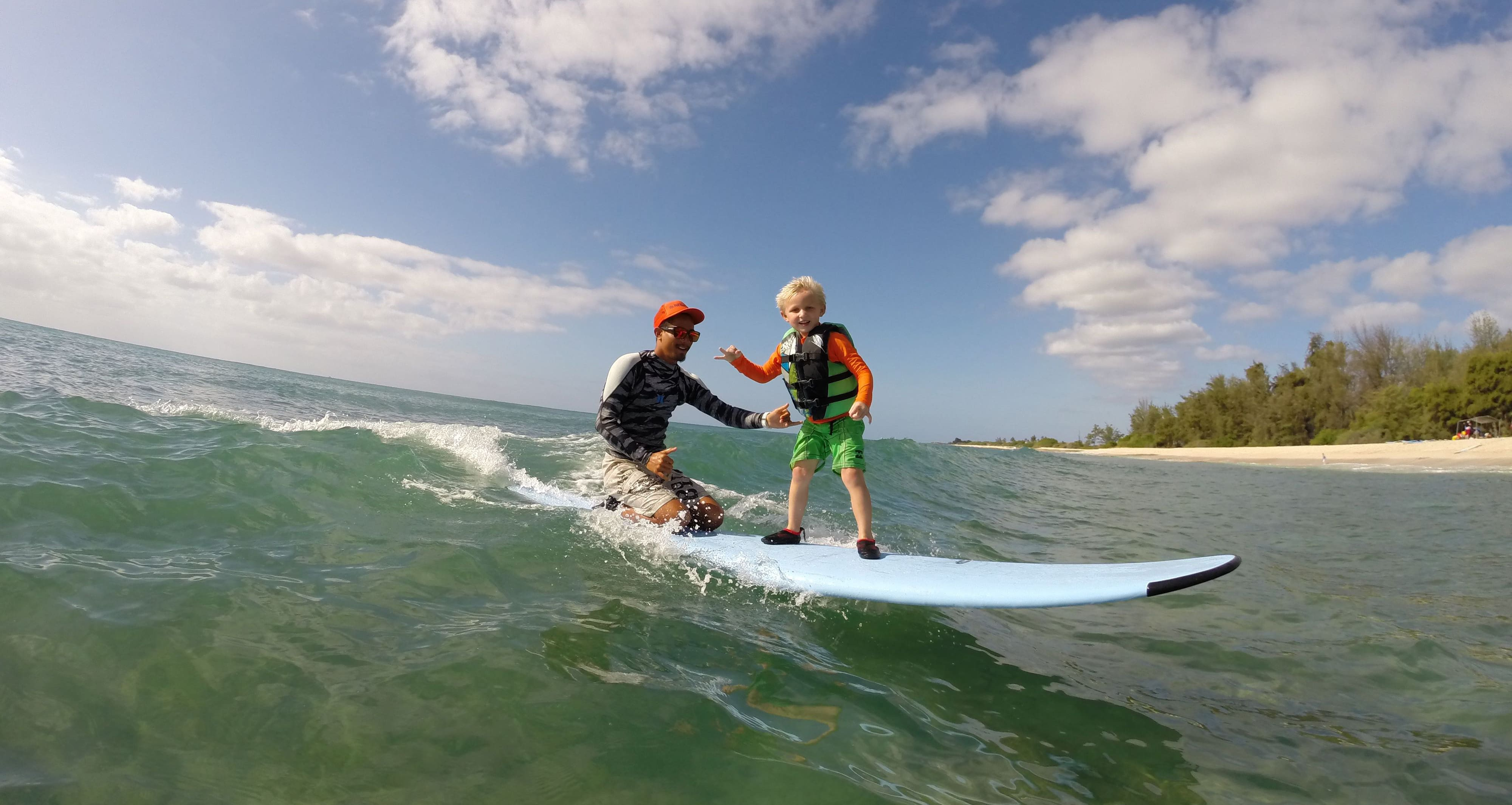 A young boy stands and an instructor kneels on a surfboard atop a breaking wave