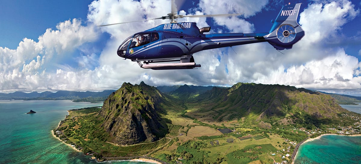 A helicopter named Blue Hawaiian flies above the lush island of Oahu and one of its shorelines