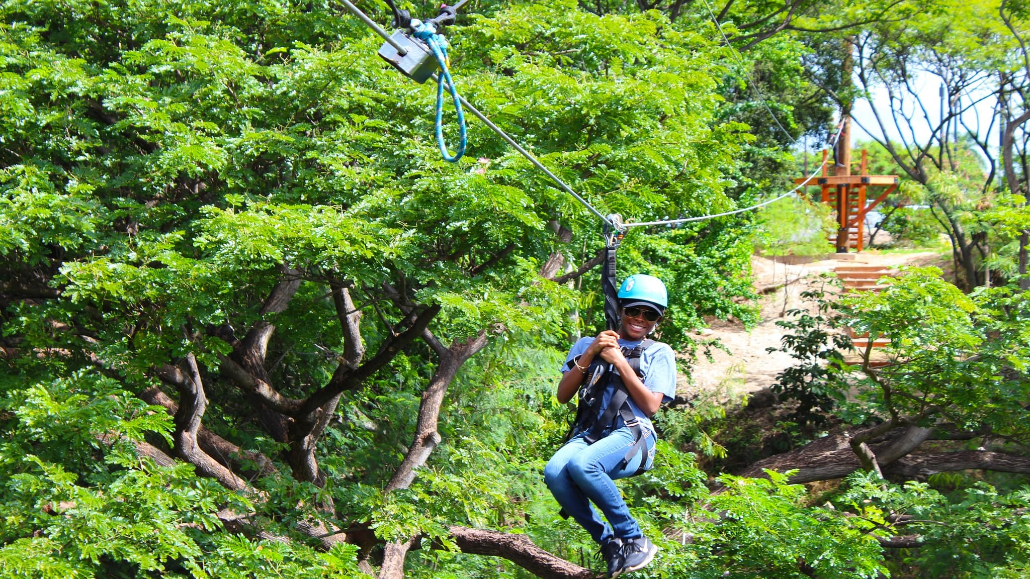 A helmeted rider on a zip line traversing a canopy of trees