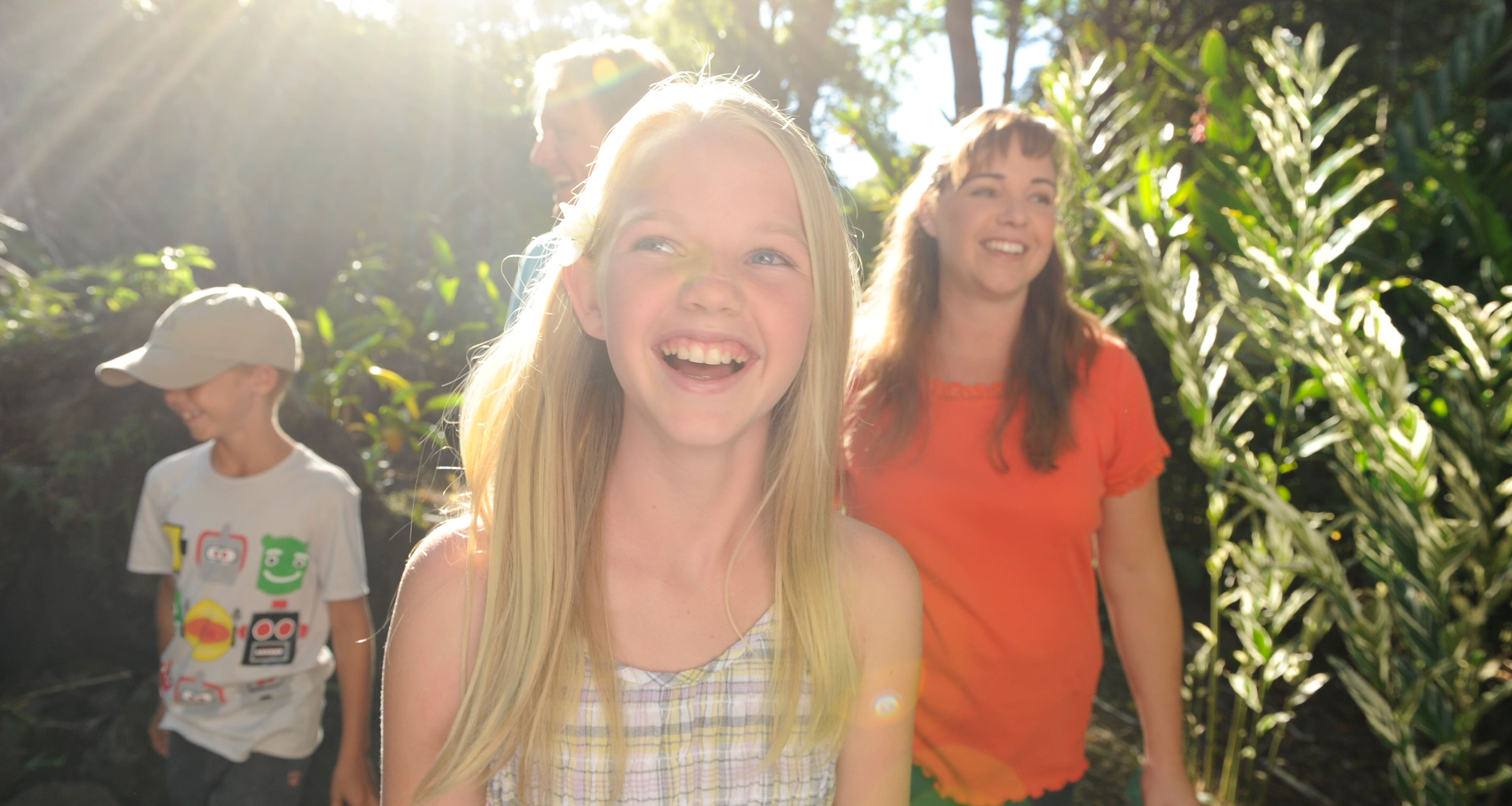A smiling girl leads her mother, father and brother on a sun-dappled path through a tropical forest