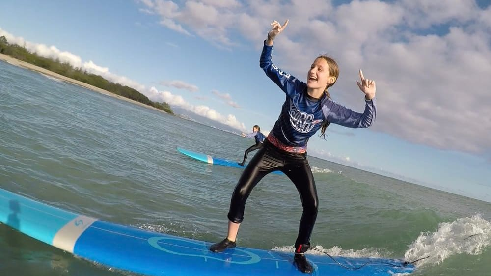 A teenage girl rides a surfboard in the ocean and gestures gleefully