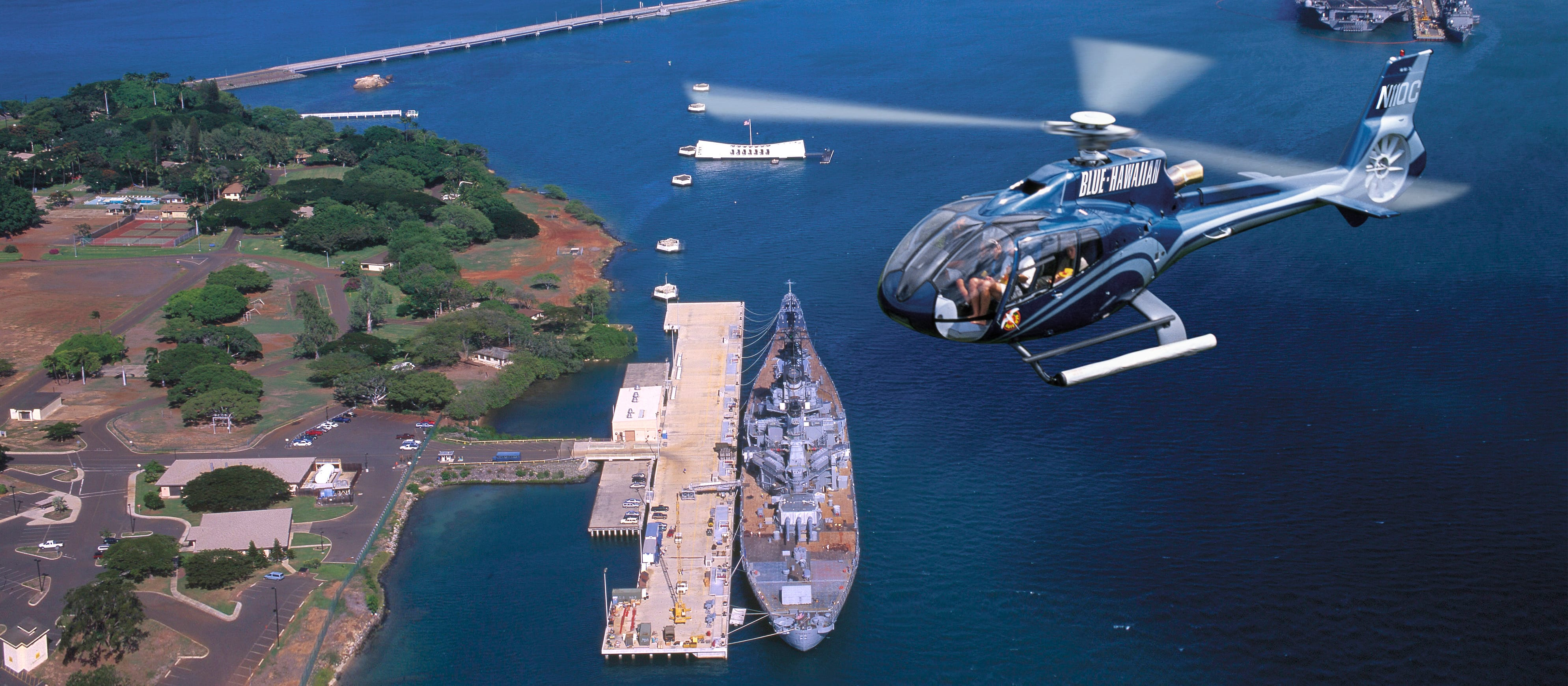 A helicopter flies over the water near Pearl Harbor