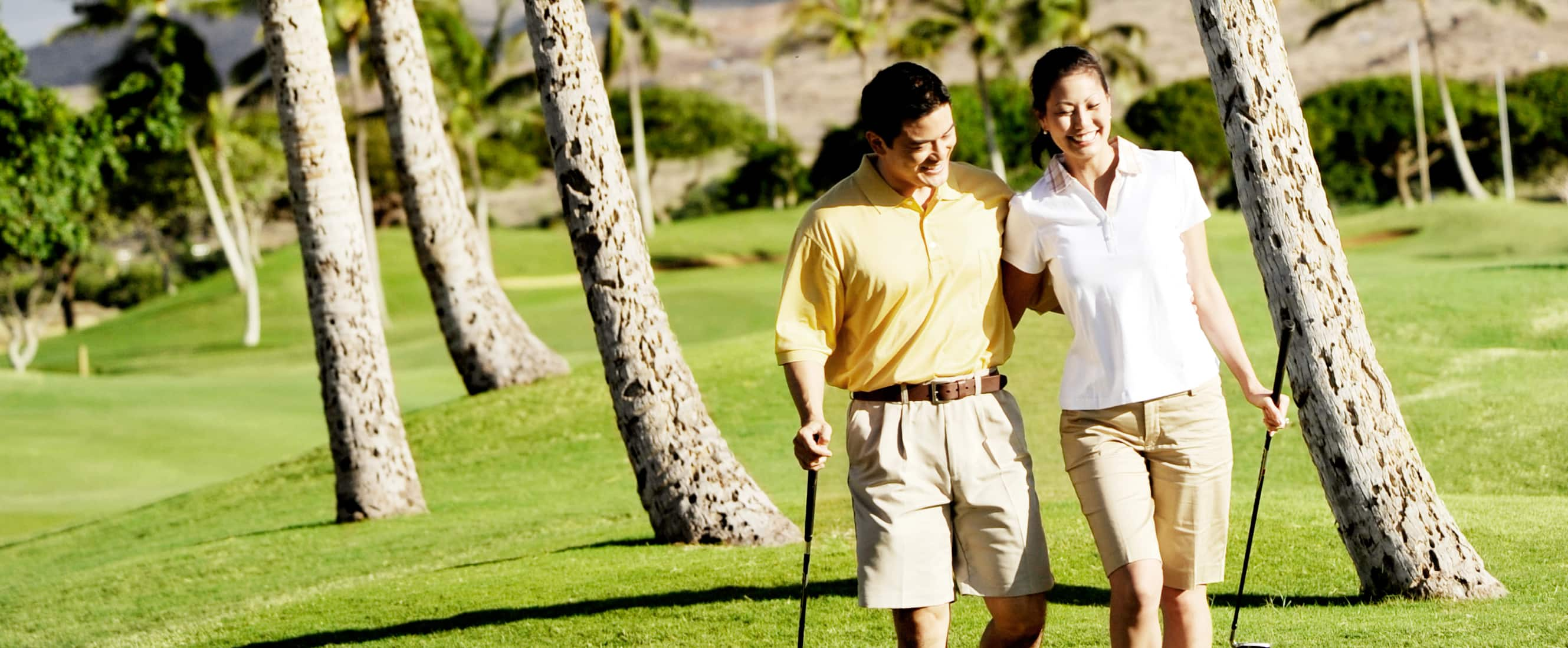 ゴルフクラブを持ち、互いの背中に腕を回してグリーンを歩く男性と女性