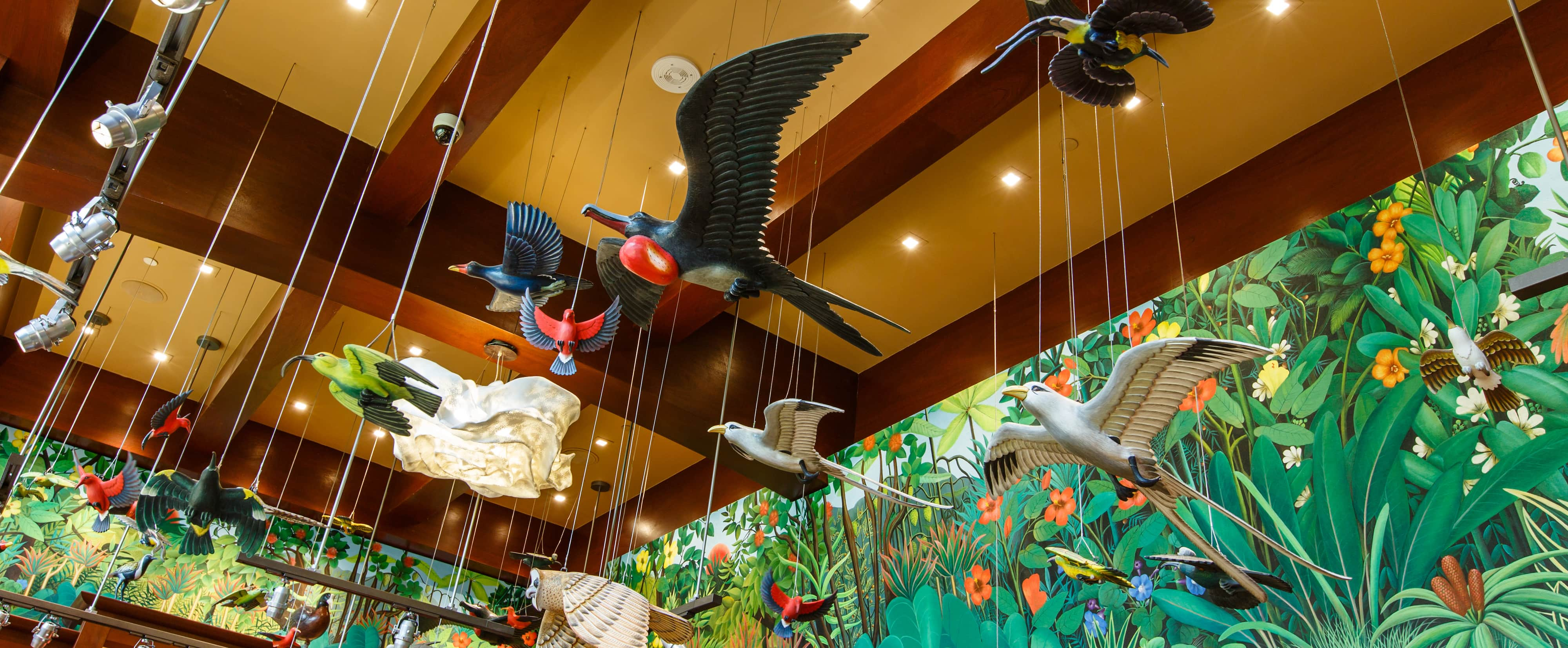Life-sized wooden birds on strings hang from a wood-beamed ceiling bordered by a mural of tropical foliage