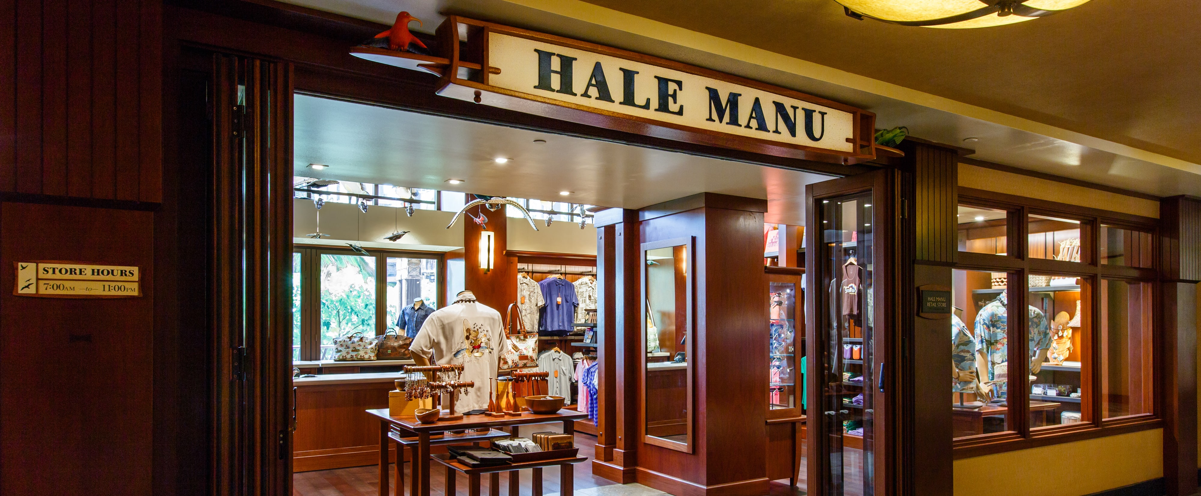 ... The wood-paneled exterior of Hale Manu boutique, with displays of resort wear and ...