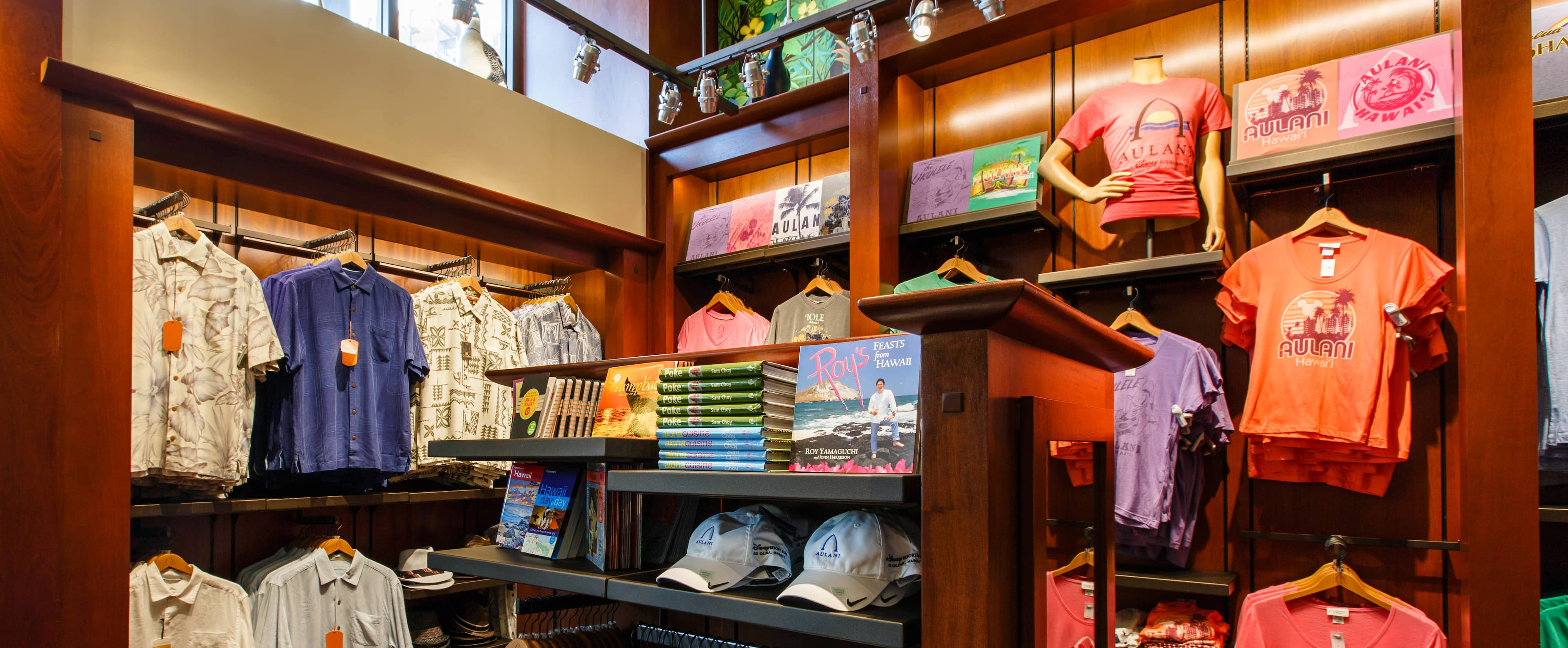 Aulani Resort caps and books about Hawaii on a shelf, with men's button-down shirts and tees hanging nearby