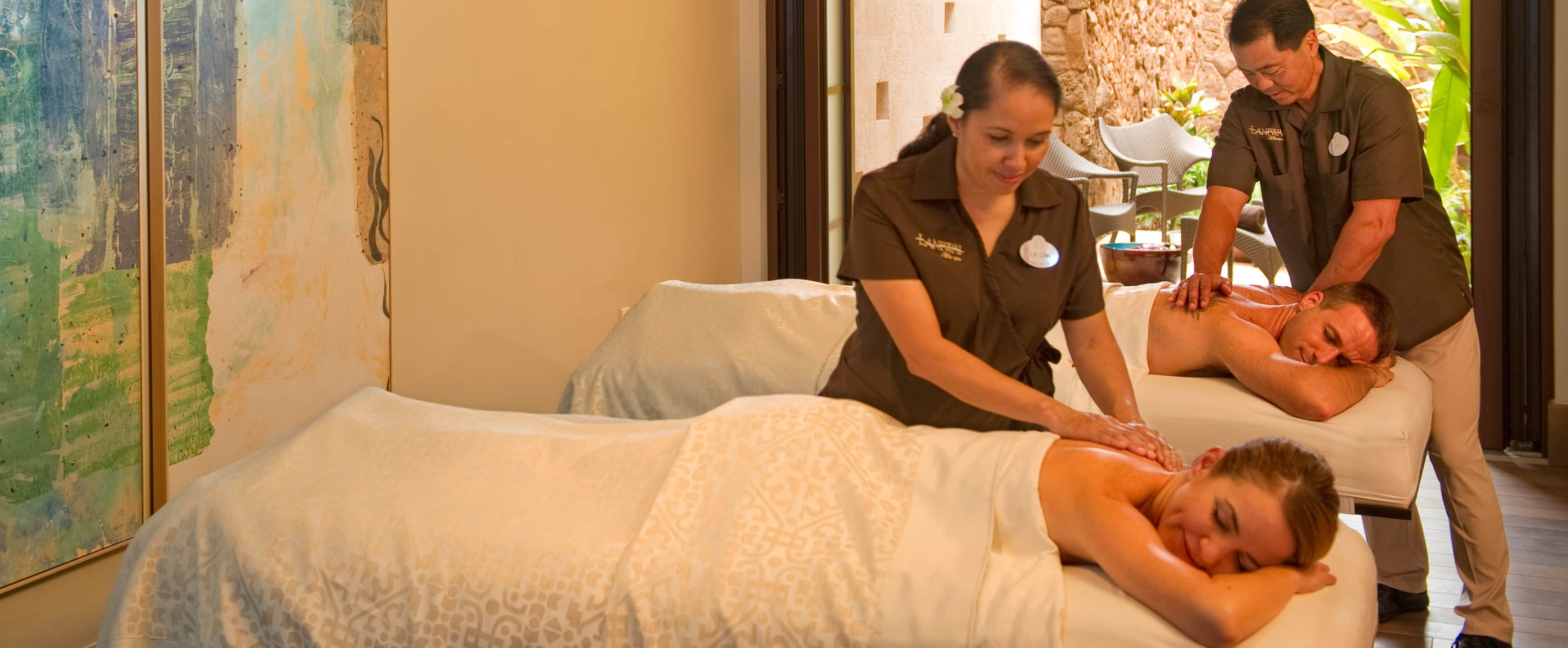 At the Laniwai spa at Aulani Resort, a man and woman relax as they receive massages in side by side beds