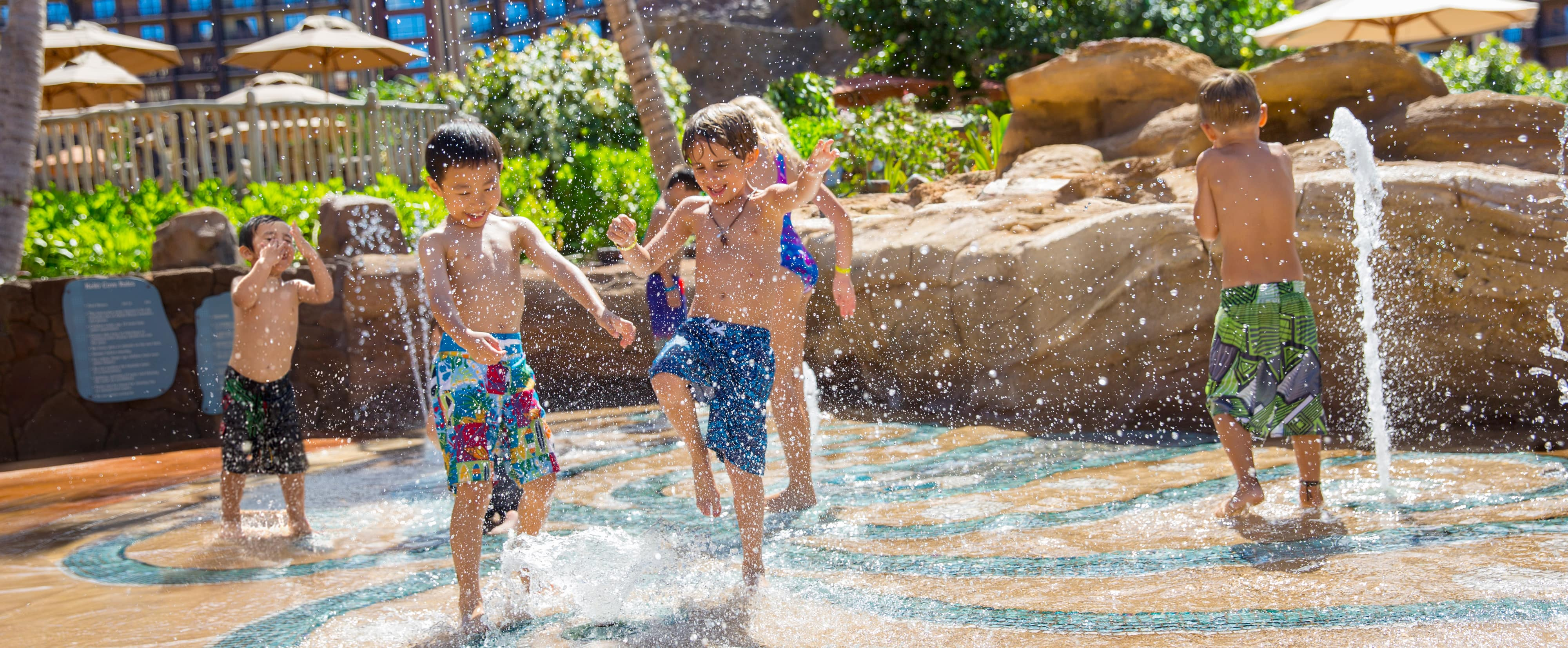 Two small boys in swim shorts frolic in a paved area with squirting water jets while 4 more children play