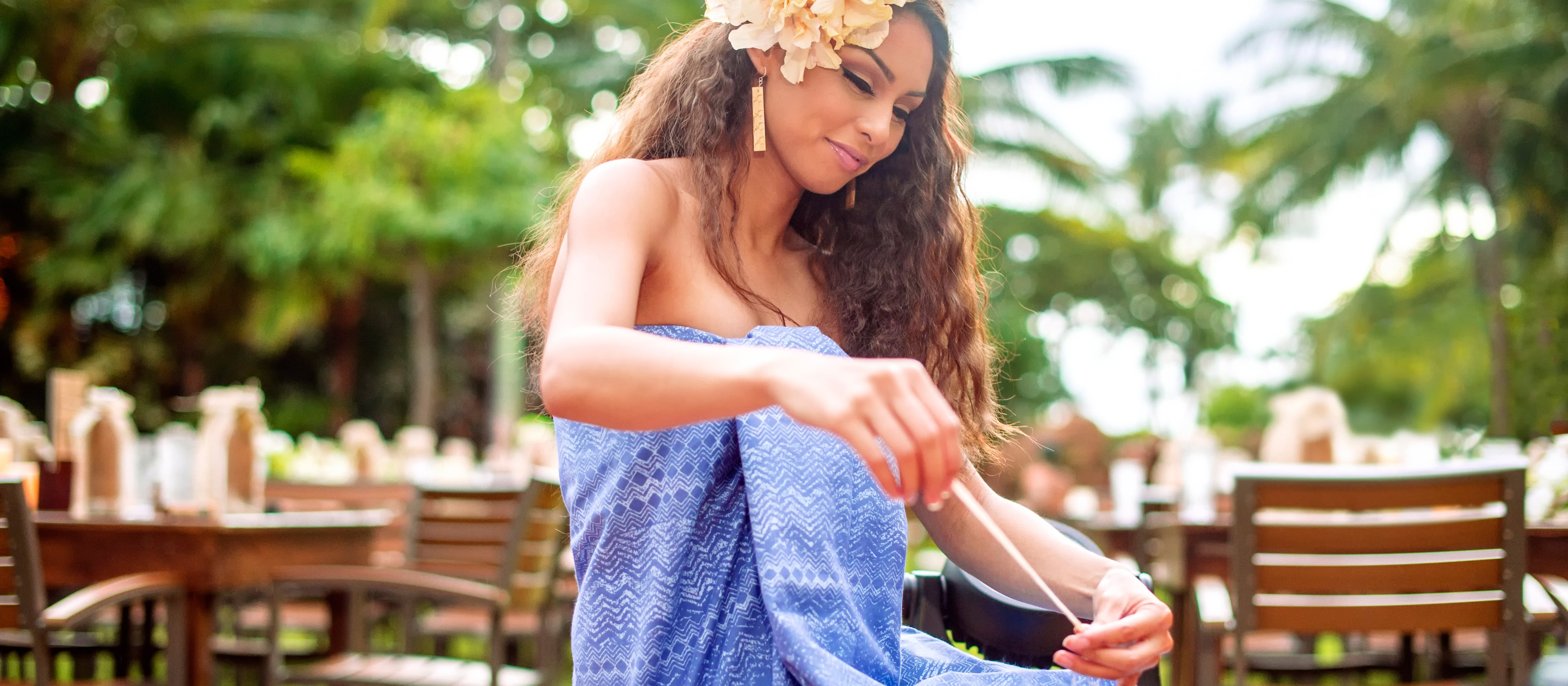 A woman with a beautiful flower in her hair smiles as she prepares string to make a lei in the luau seating area.