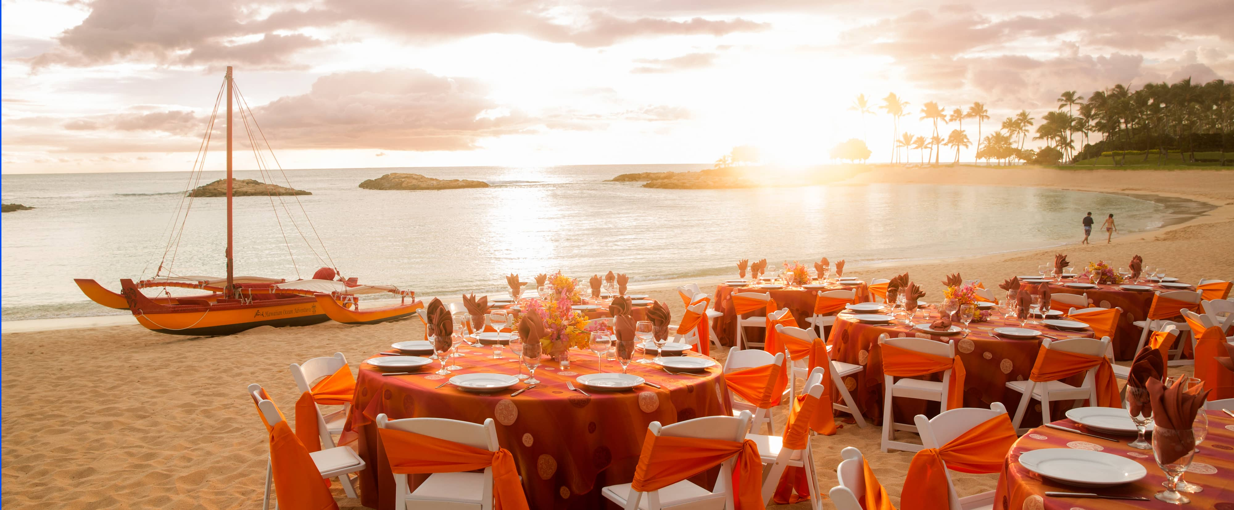 Festively set tables and chairs are grouped in the sand along the beachfront