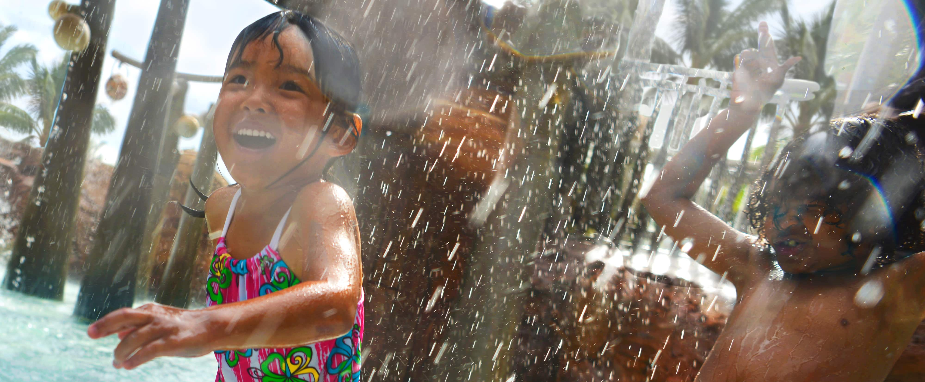 メネフネ・ブリッジのプレイエリアで、流れ落ちる水の下で笑いながら遊ぶ男の子と女の子