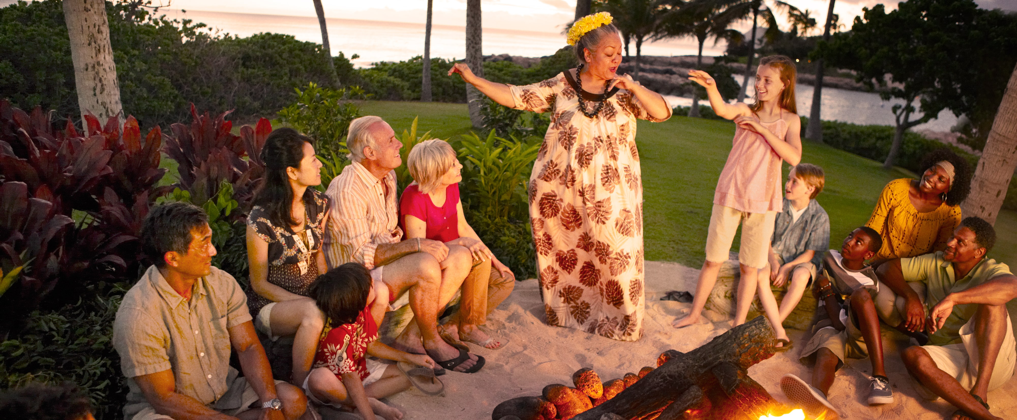 A woman in Hawaiian garb teaches a girl hula hand motions while the rest of the group watches by the fire