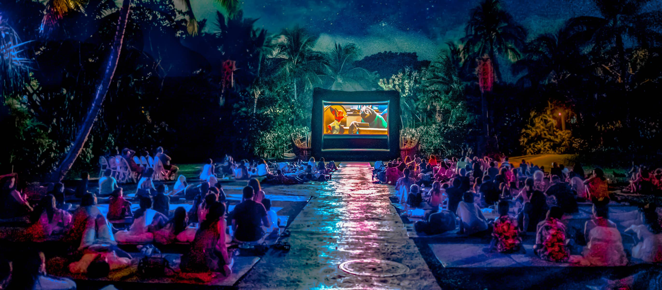 Guests seated on a large lawn, watching a movie screening after dark