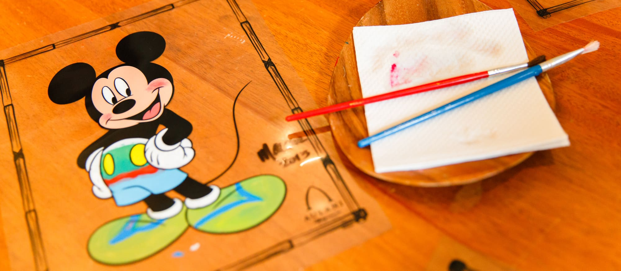 An illustration of Mickey Mouse on a wood surface adjacent to a dish with paintbrushes resting on a napkin