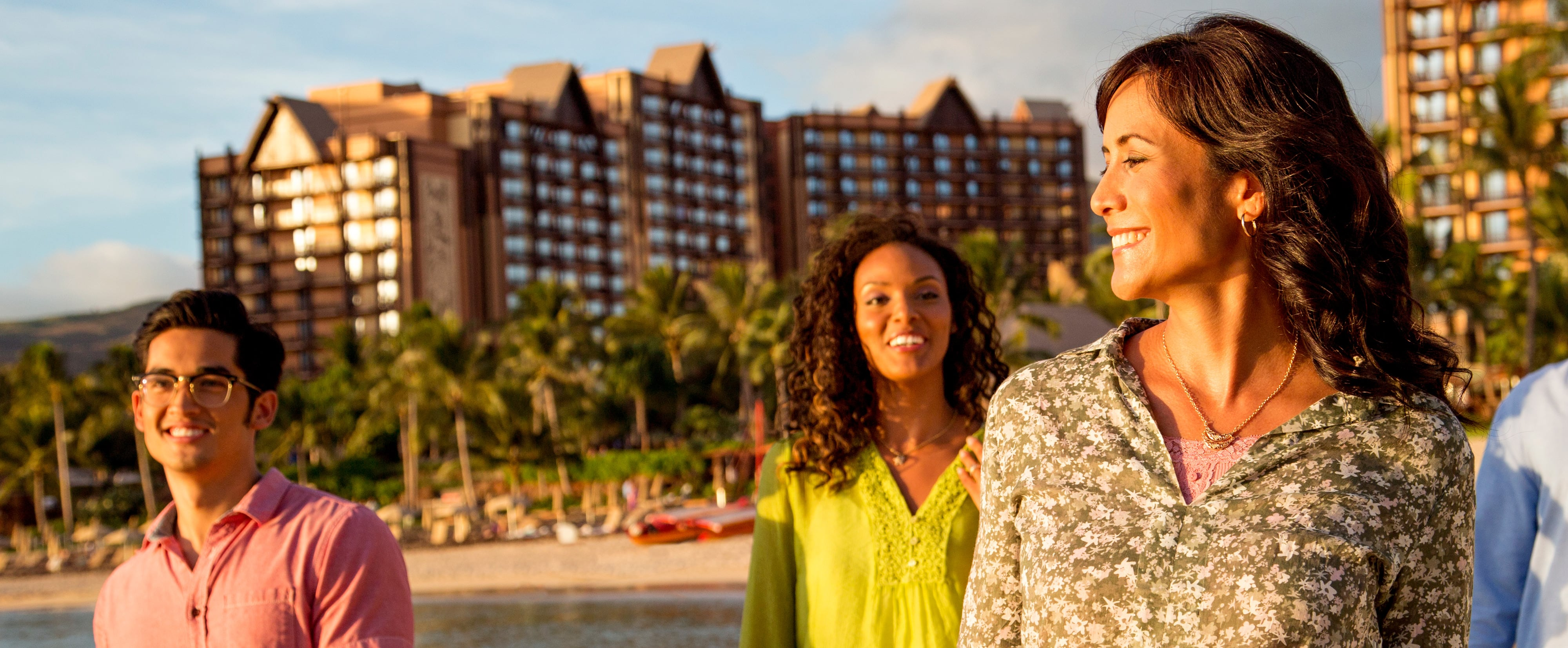 A young man and two young women walk along the beach in front of the Aulani Resort.