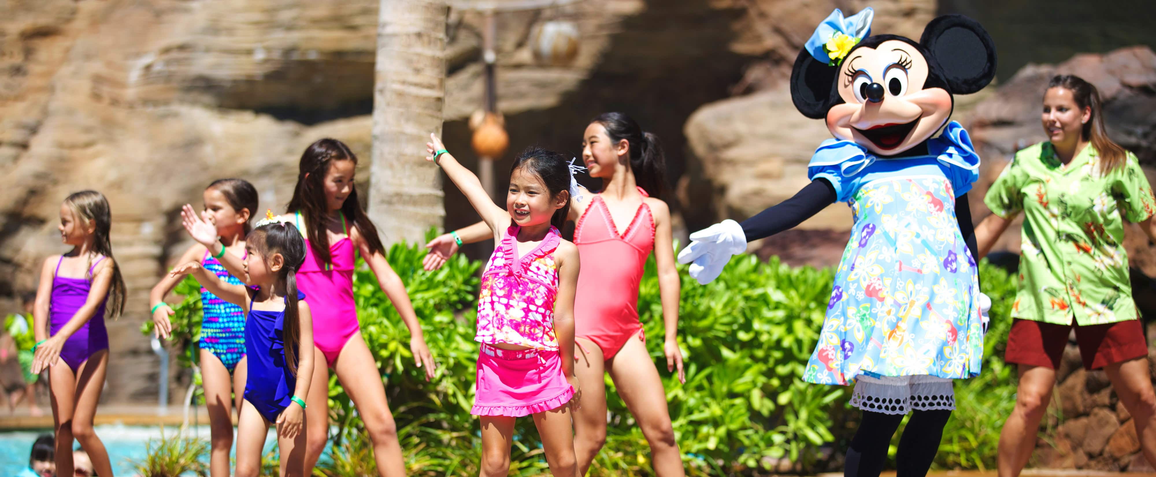 Minnie and a group of young girls strike a pose while dancing poolside